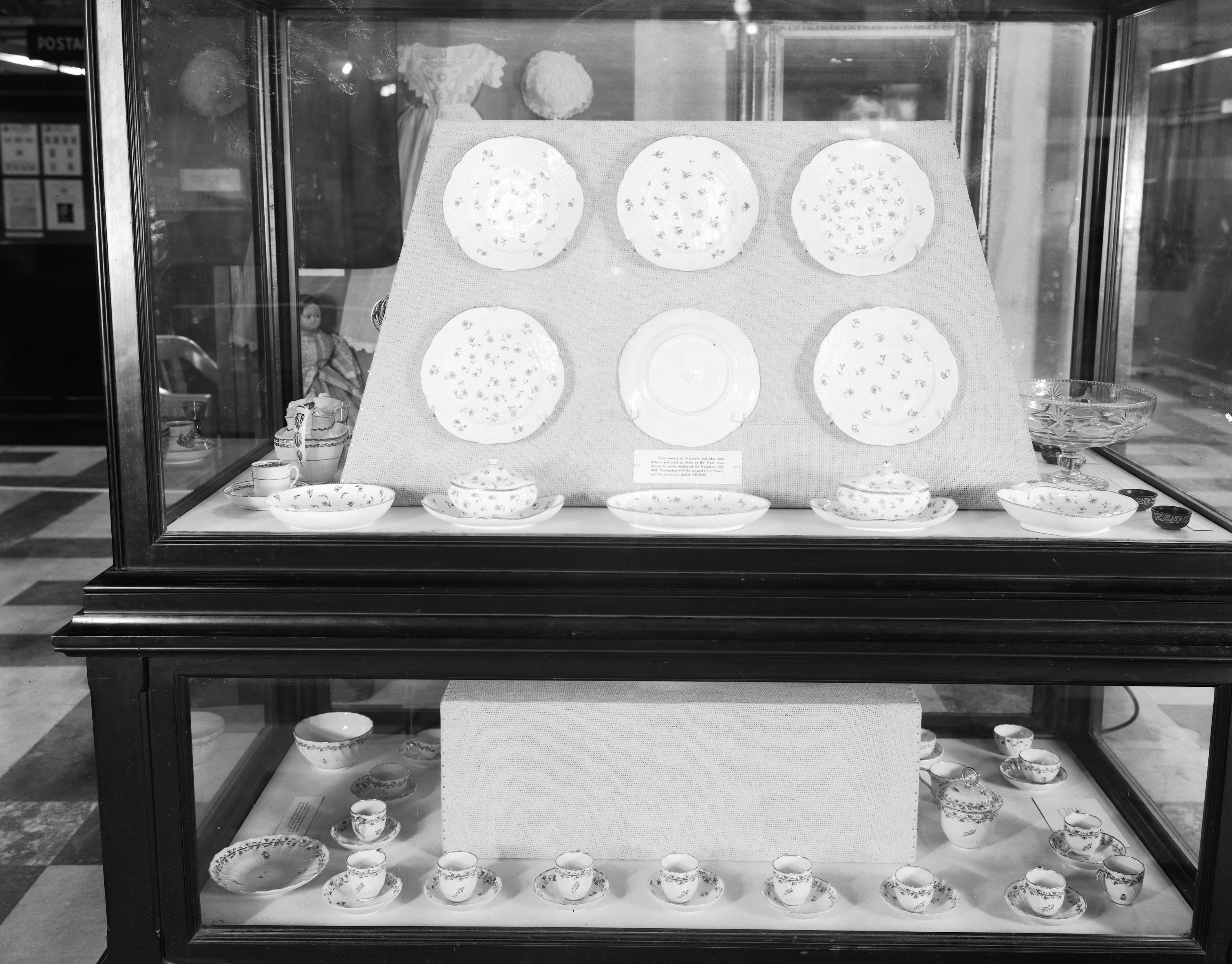 Exhibit case of china and a tea set. The case has upper and lower portions.