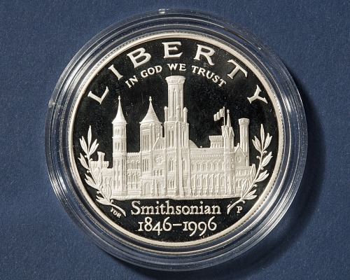 This silver coin depicts the Smithsonian Castle and laurel branches (obverse) and an allegorical fig