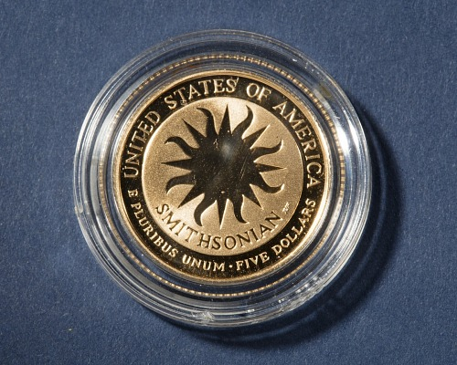 The gold coin depicts James Smithson (obverse) and the Smithsonian's sunburst logo (reverse) with an