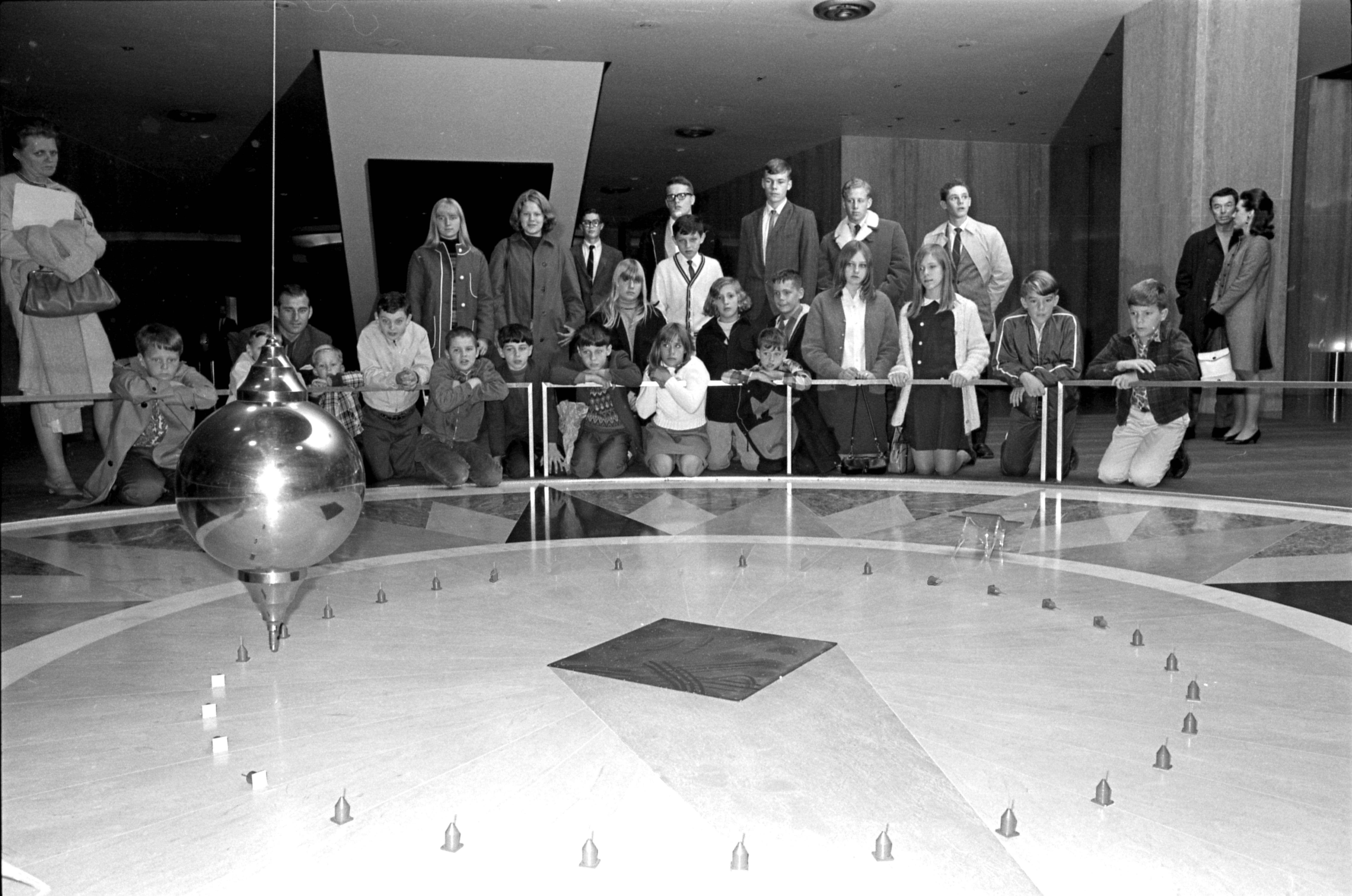Black and white photo of a crowd of people in a museum watching a Foucault pendulum knock over pegs.