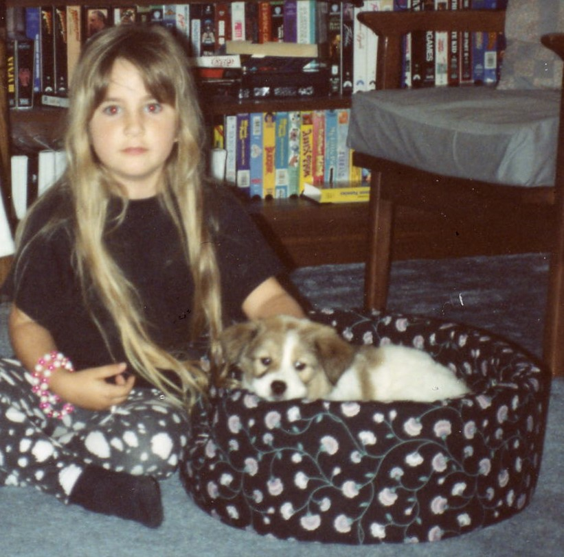 Young person with small dog in bed.