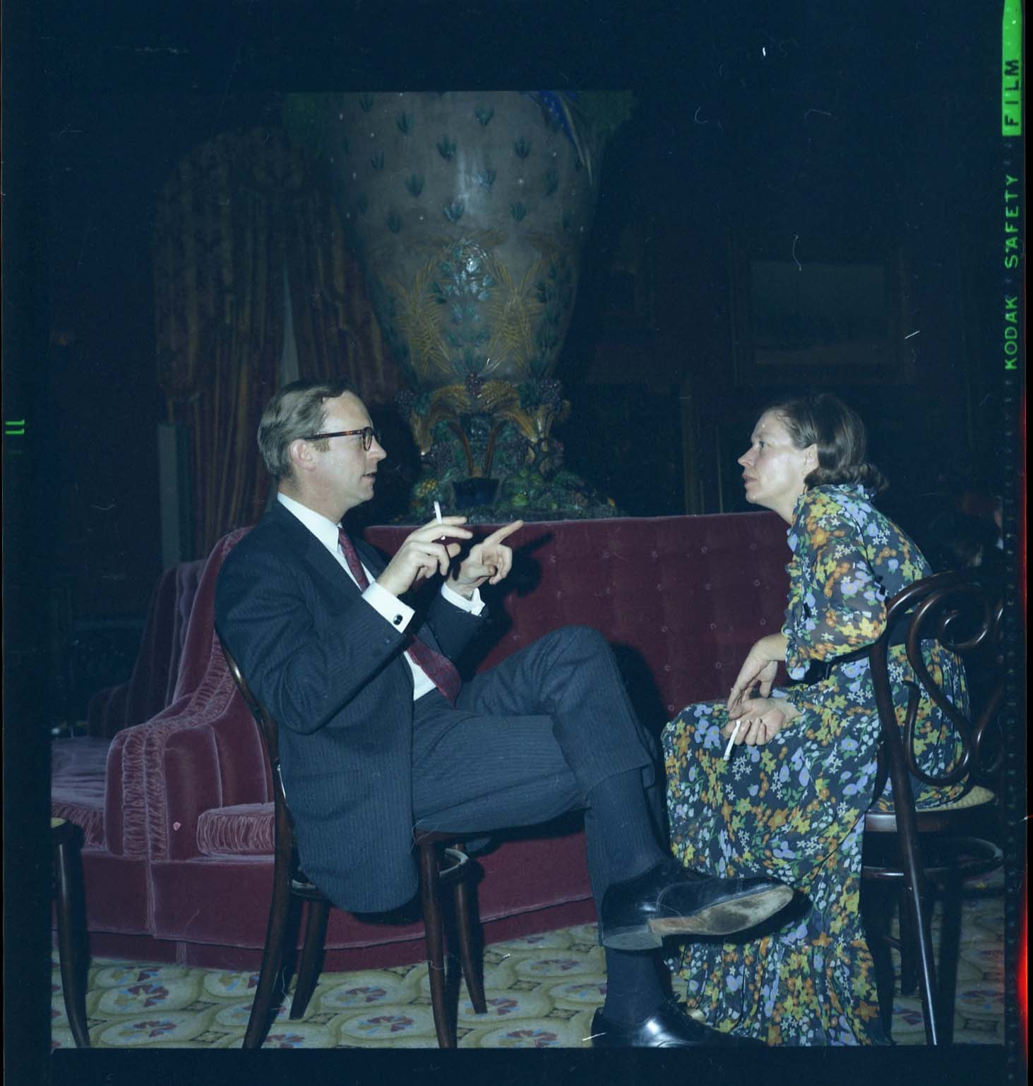 A man and woman sit and talk. The man is holding a cigarette.