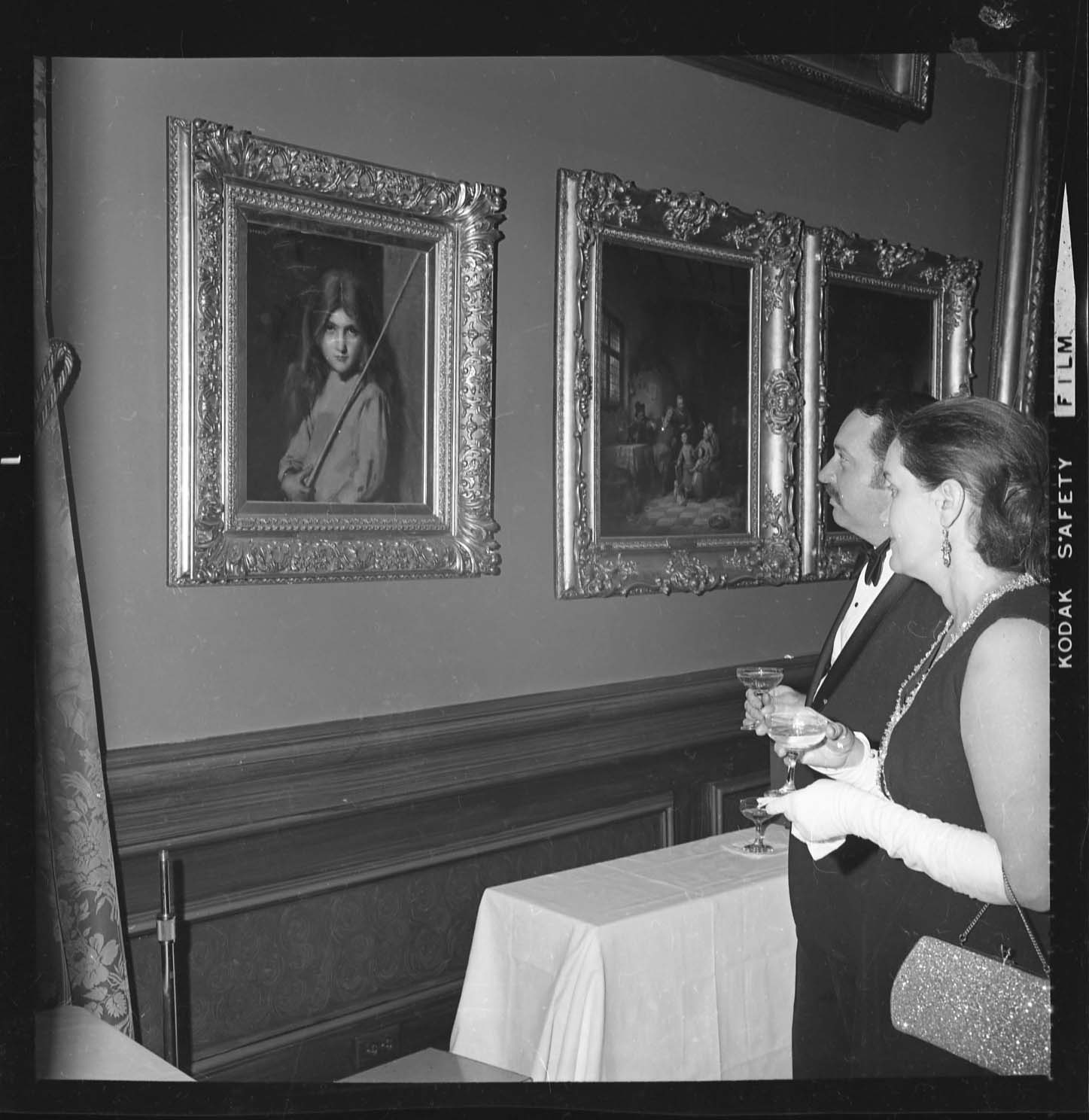 A man and woman hold drinks and look at a portrait hanging on the wall.