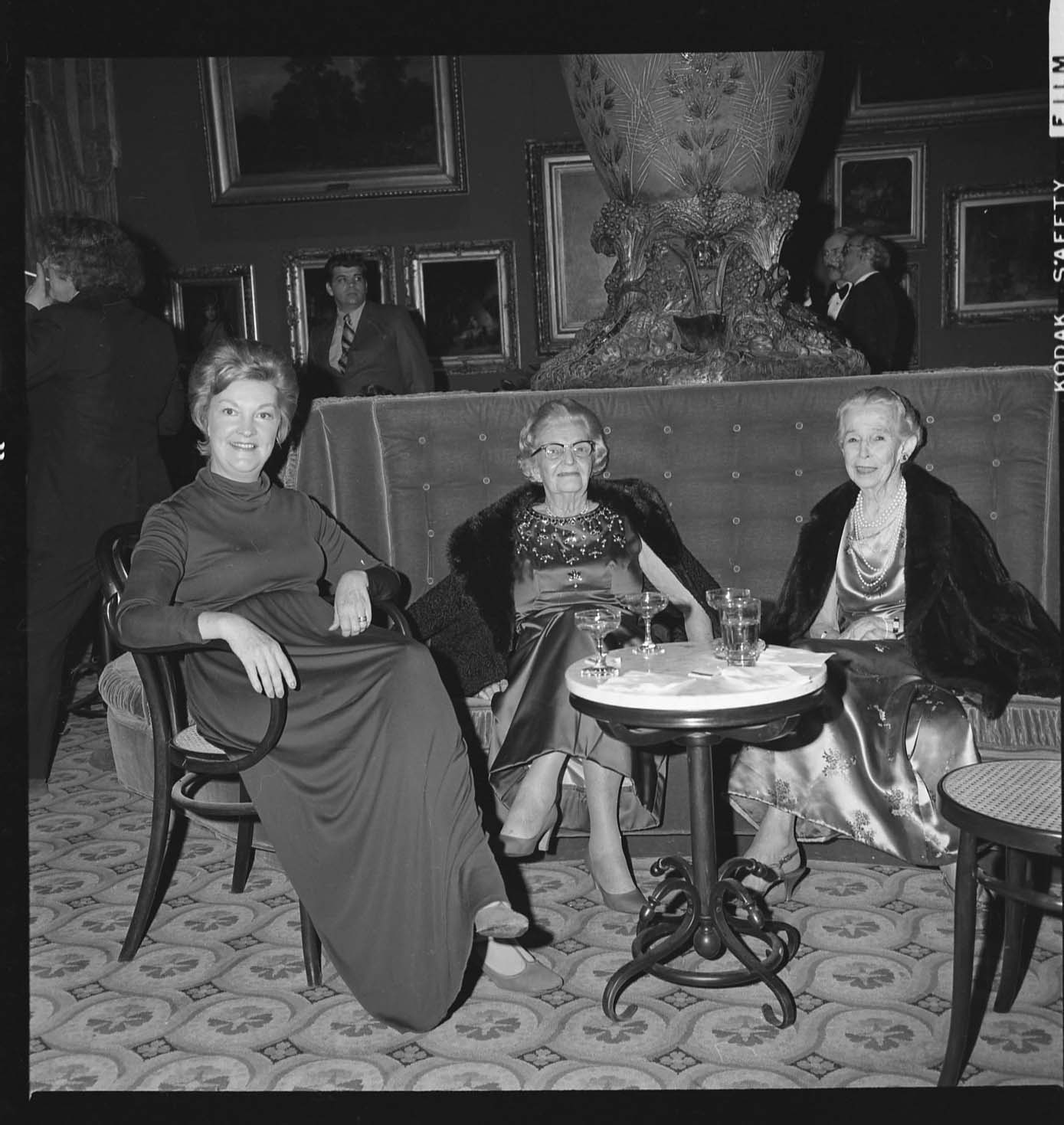 Three women sit at a table around empty glasses.