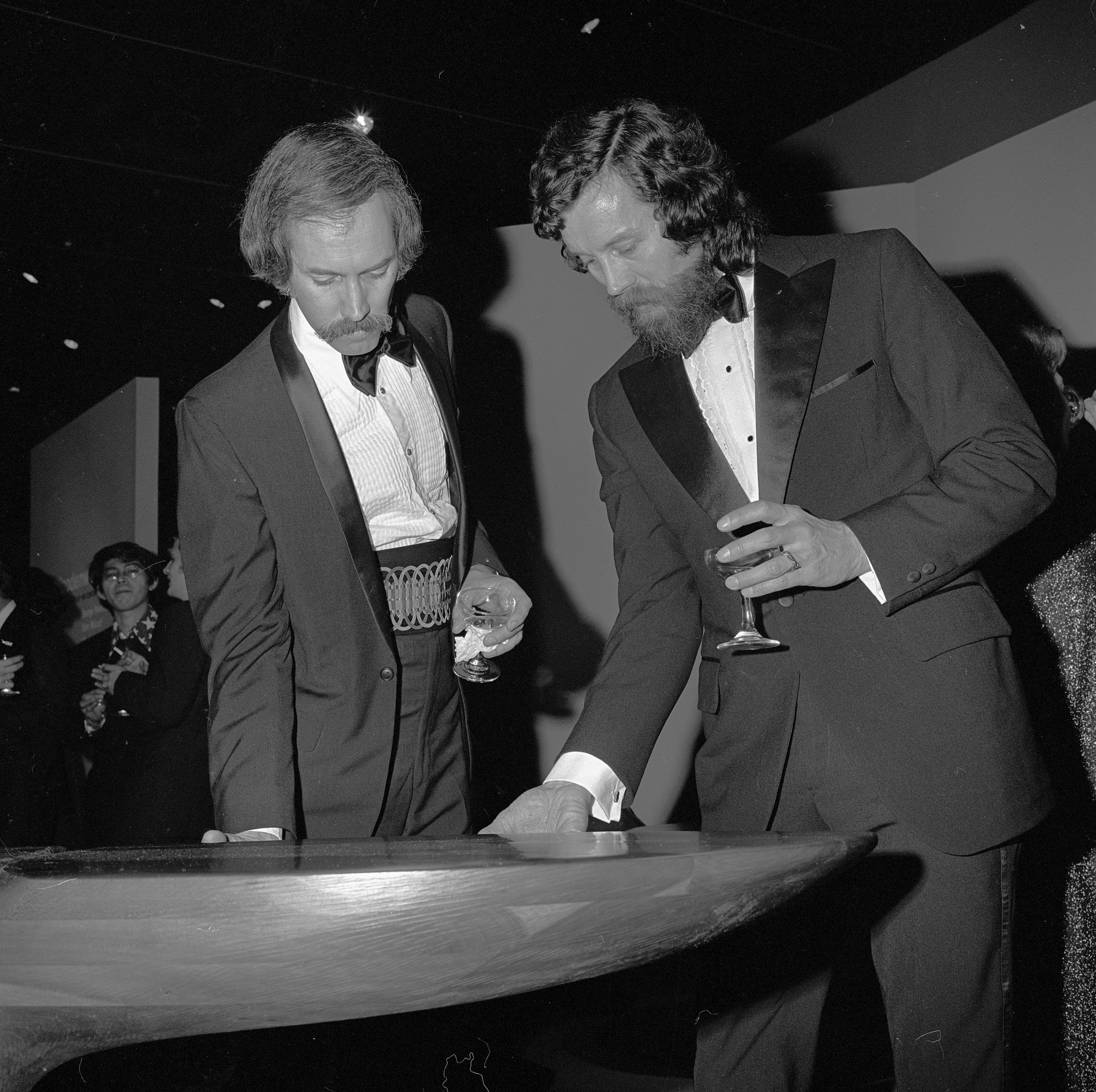Two men stand over a wooden table. Both are holding drinks.