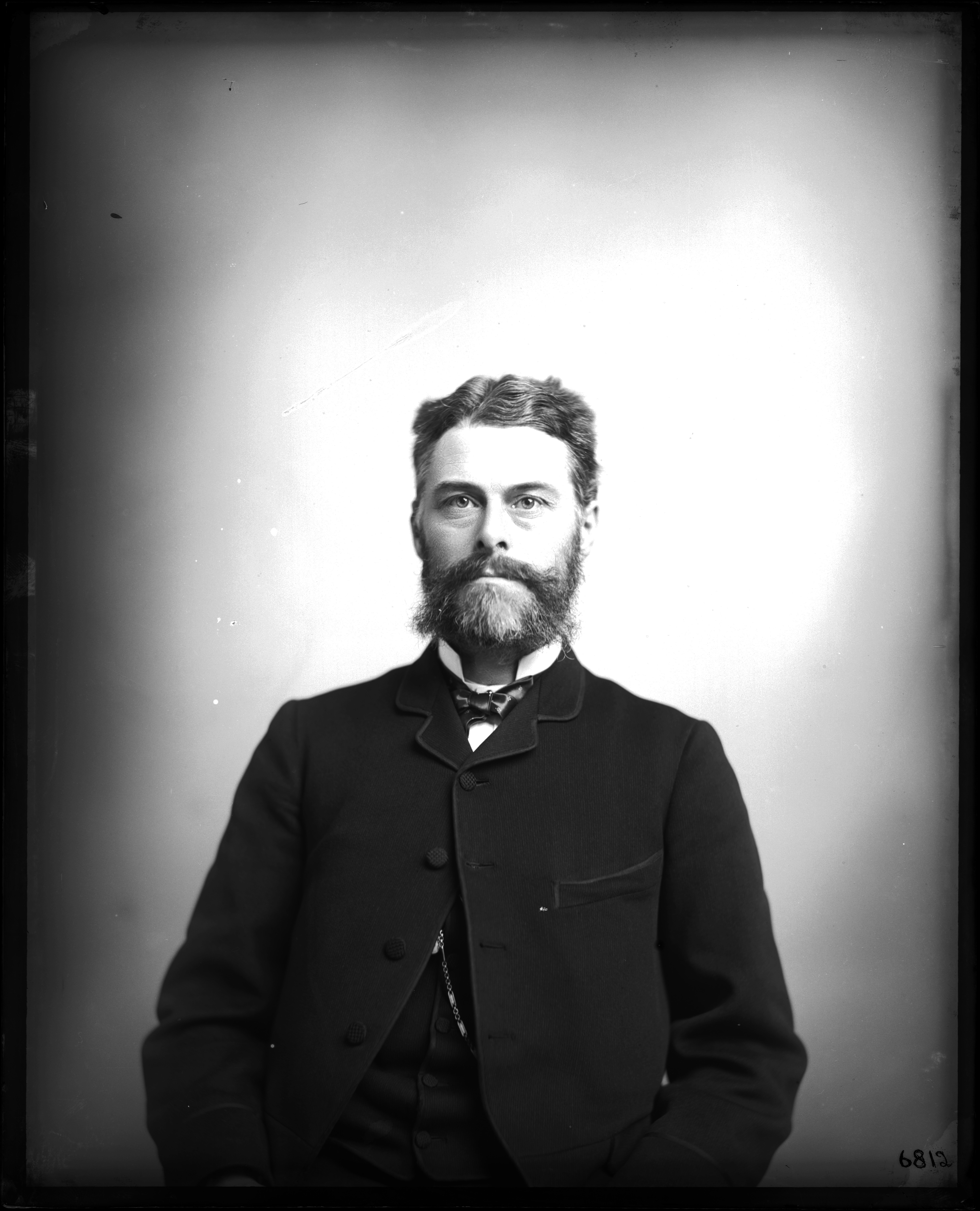 A man in a suit and bowtie stares directly into the camera. He has a beard.