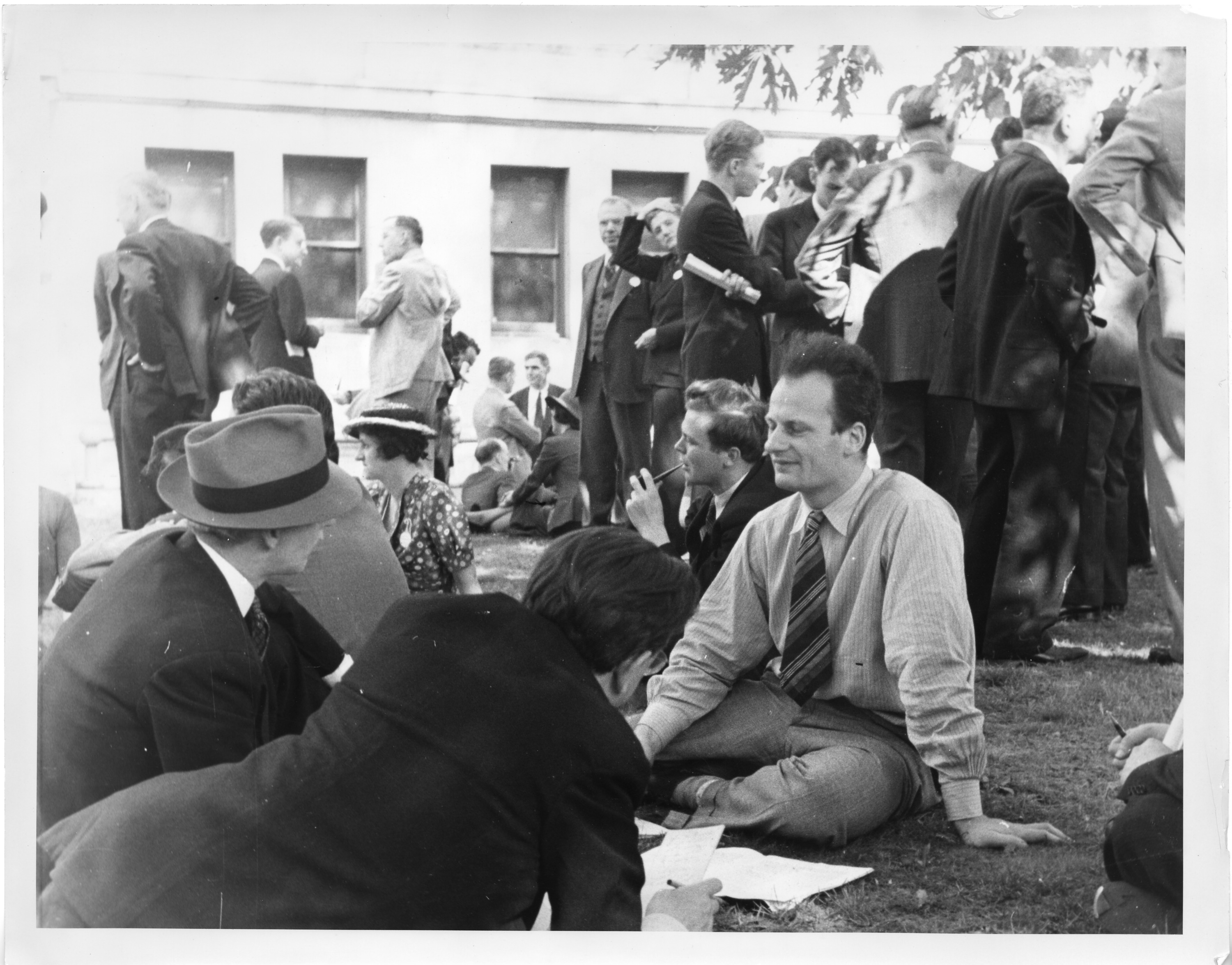 Men and women sit and stand on a lawn outdoors. All are wearing suits or dresses. Three men closest