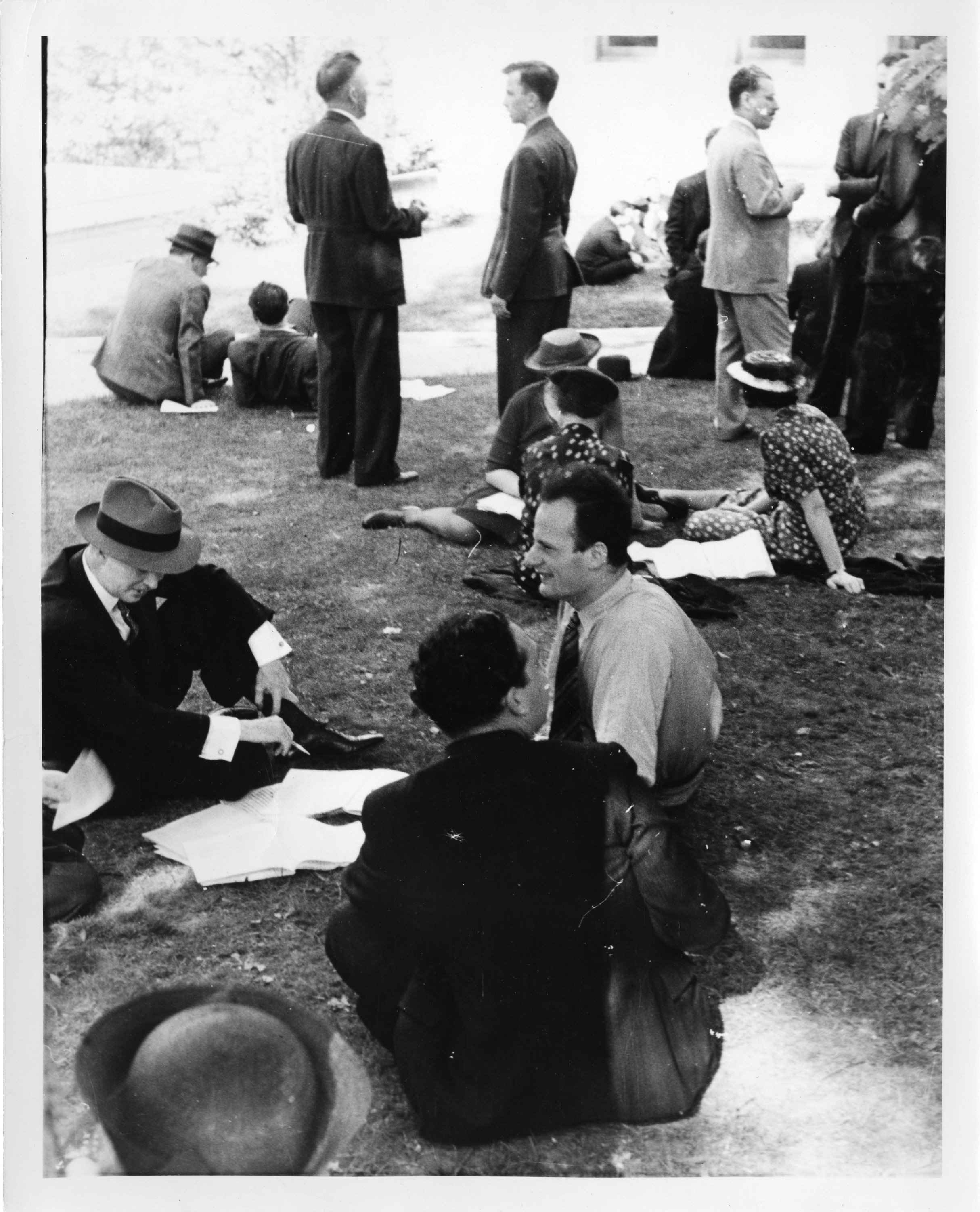 Men and women sit and stand on lawns. A few of te seated groups have papers scatter on the lawn in f
