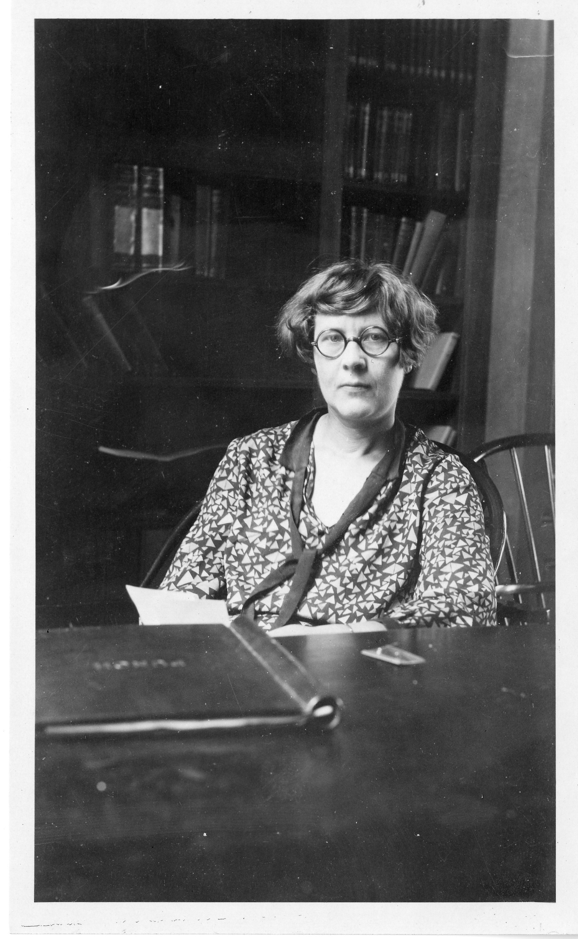 A woman with short hair and glasses sits at a desk. She has a book open.