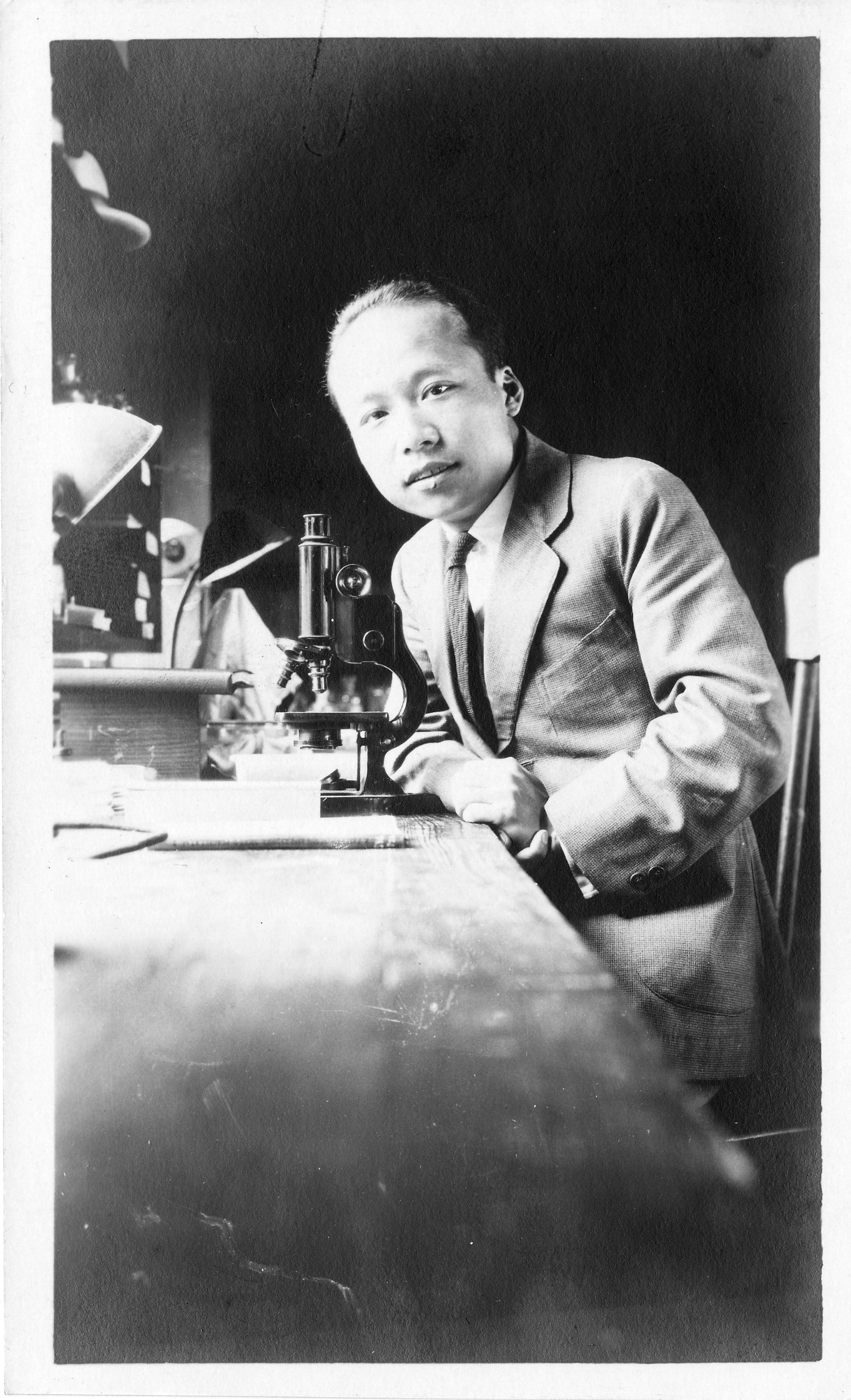 A man leans toward his desk. On the desk, his hands are near a microscope.