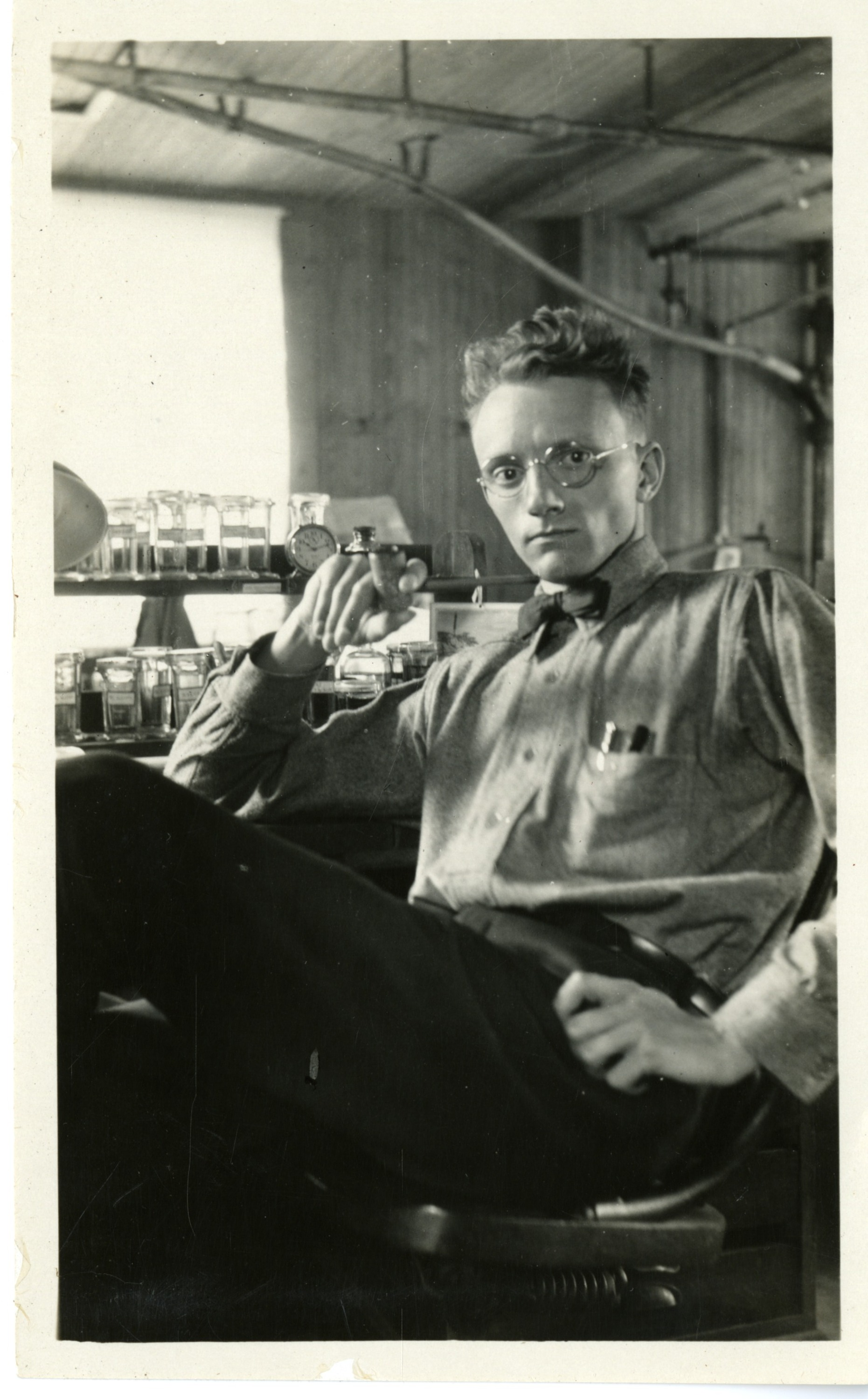 A man wearing glasses leans back near a desk. He has pens in his front pocket,