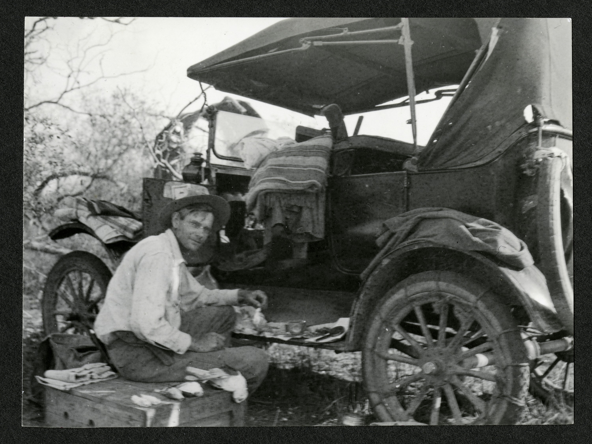 B&W image of B&W image of Alexander Wetmore sitting on a crate next to a automobile.