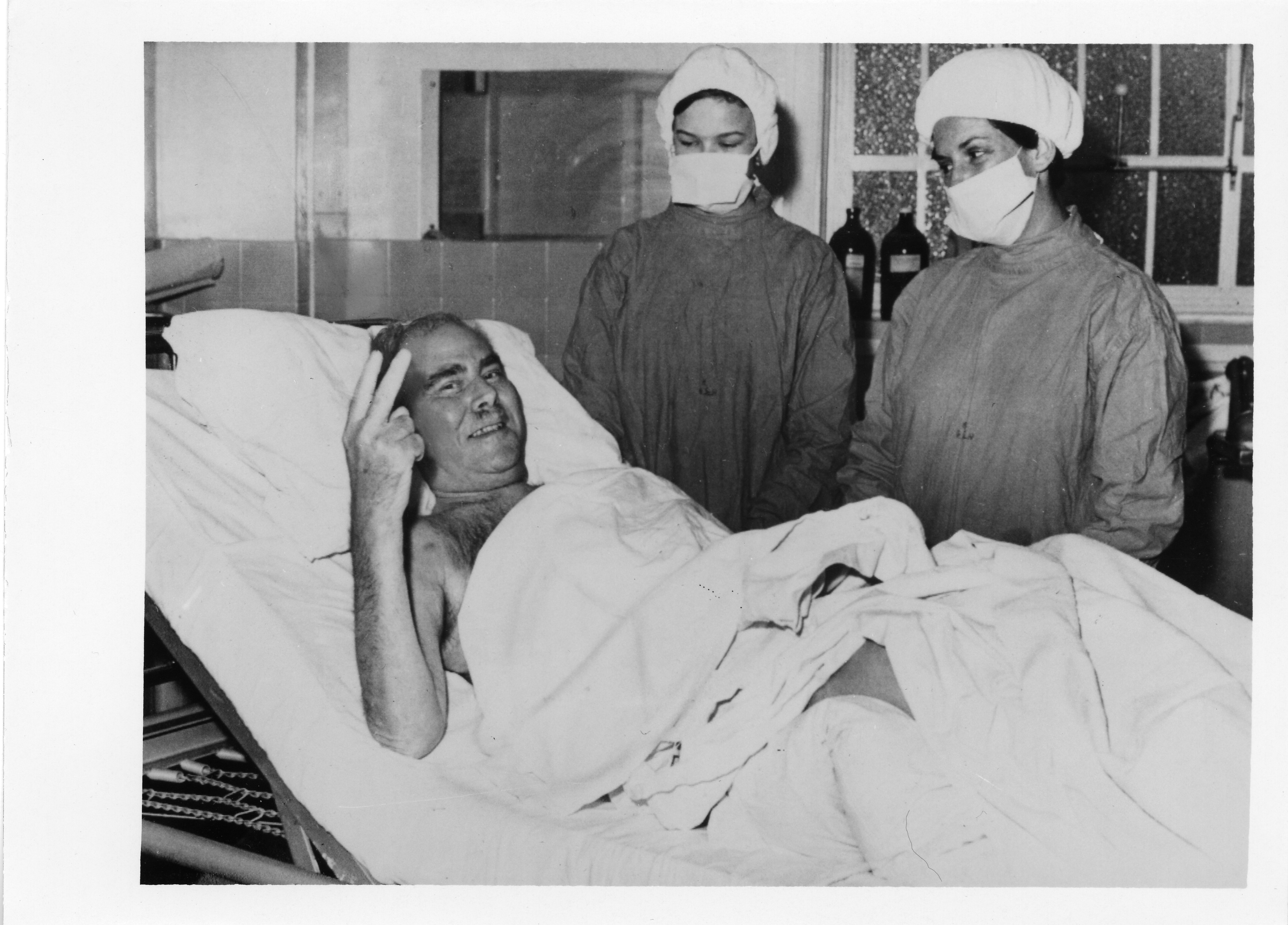 "A patient lies in bed and gives the camera a ""thumbs up."" Two hospital staff stand near the bed."