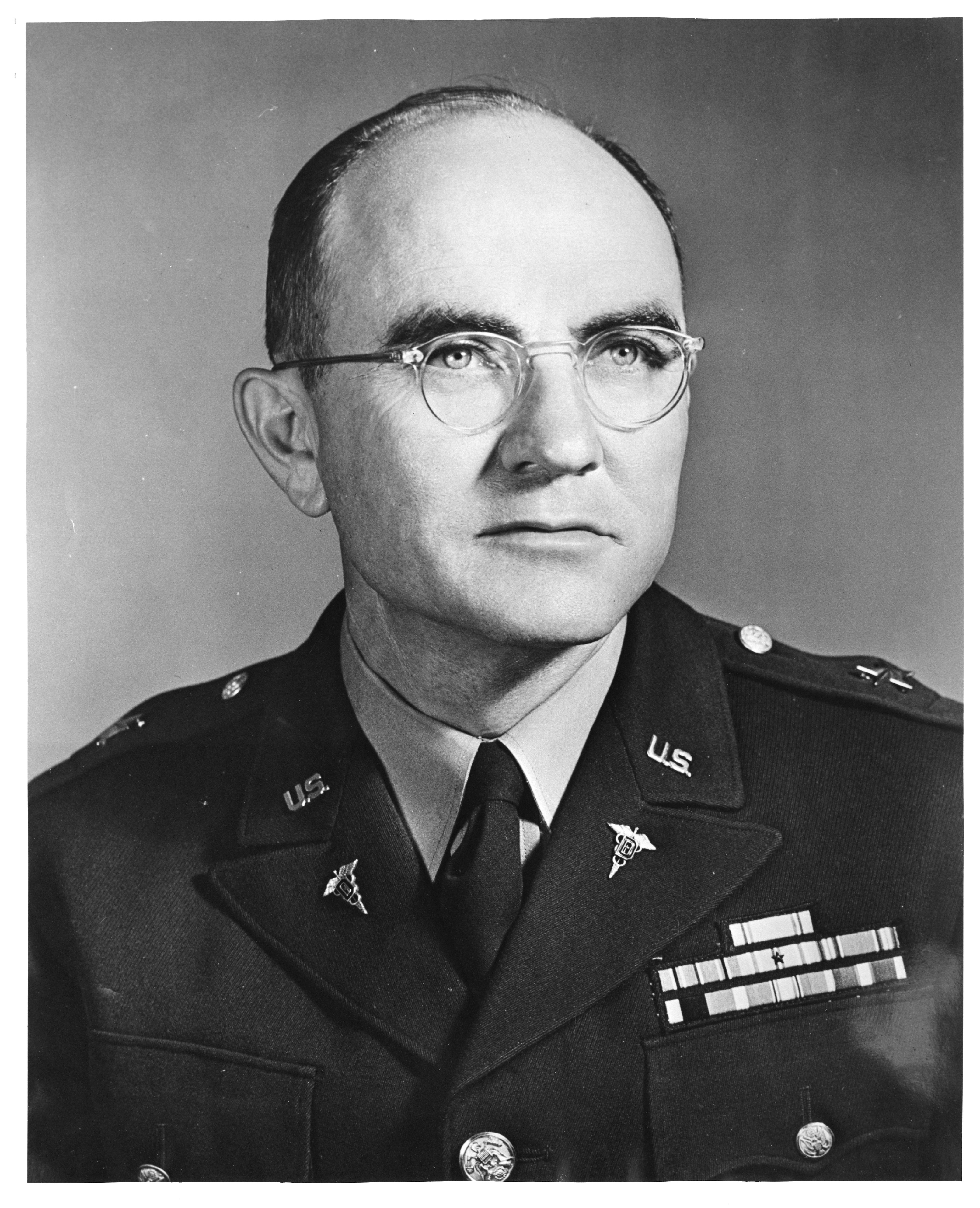 Portrait photograph of a person in a military uniform and wearing glasses.
