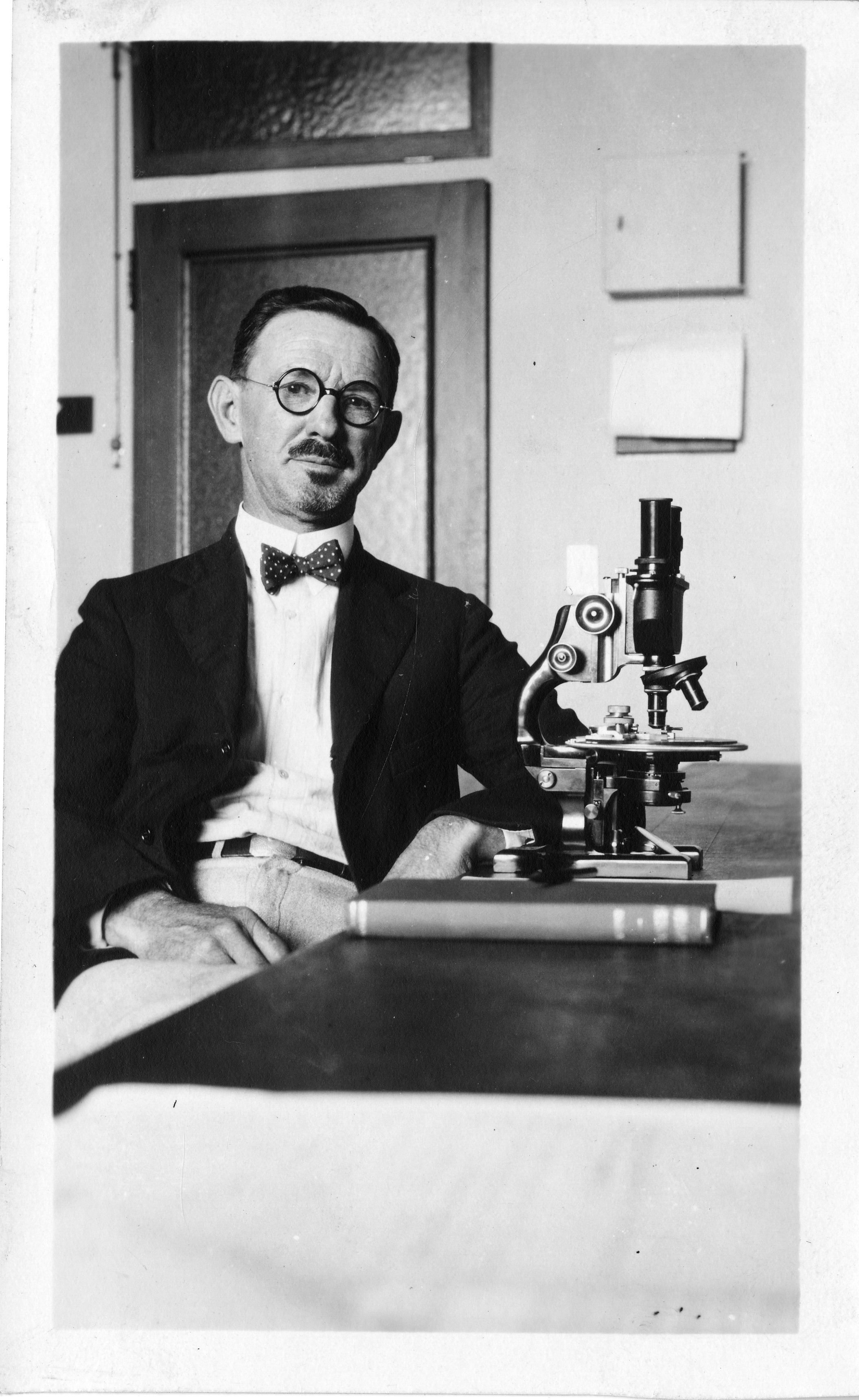 A person wearing a suit and glasses sits at a desk and looks directly into the camera. A microscope