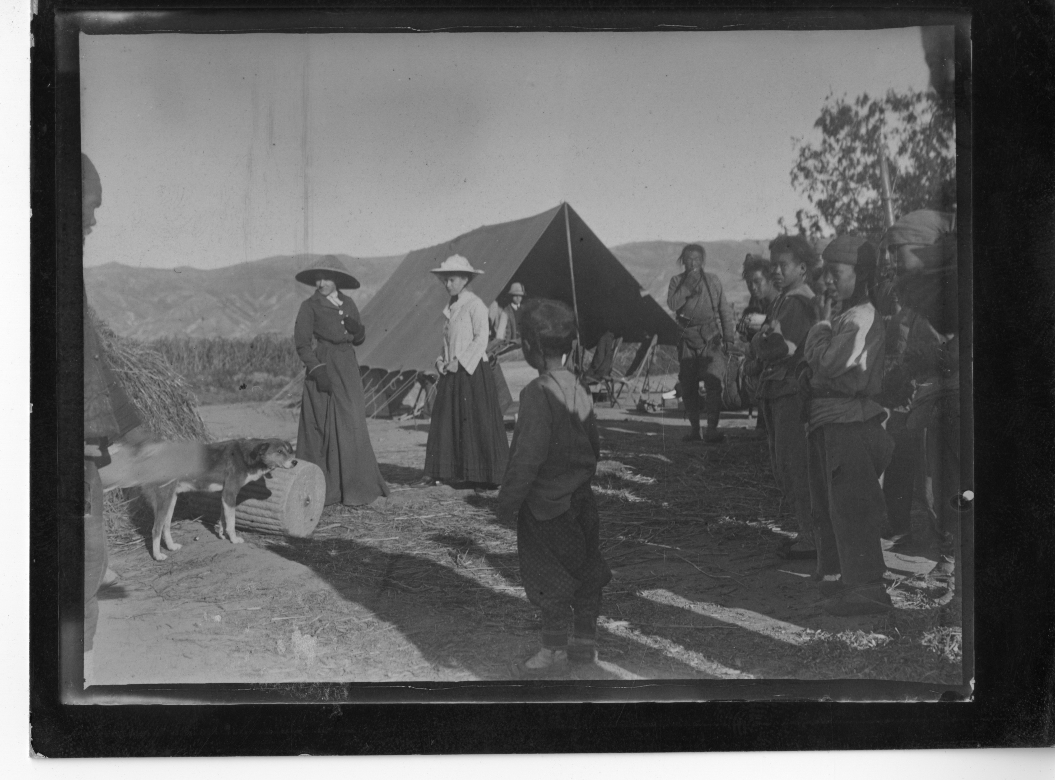 Two women at a campsite. There are children and a dog at the site. The children have darker skin.