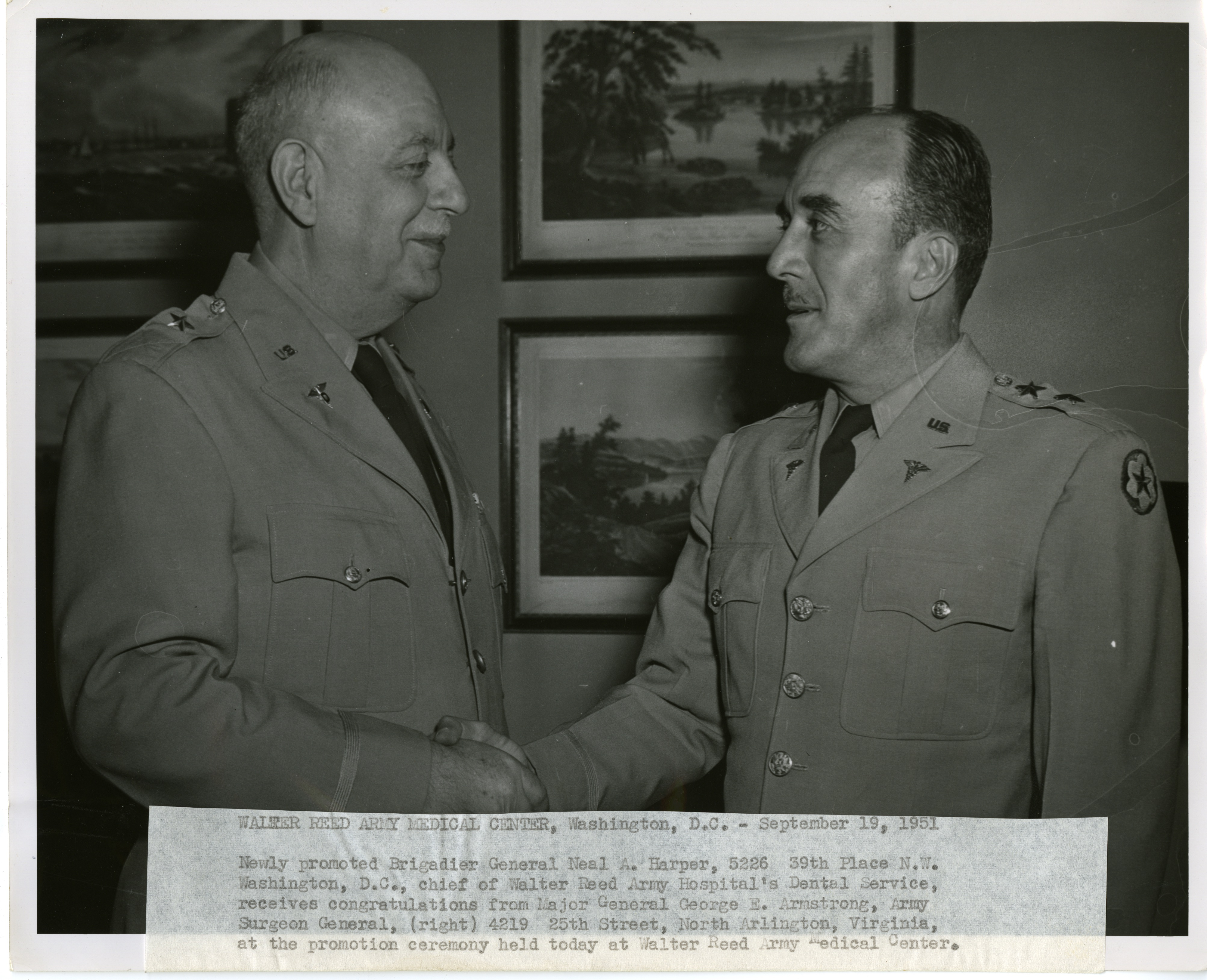 Two people in military uniforms shake hands.