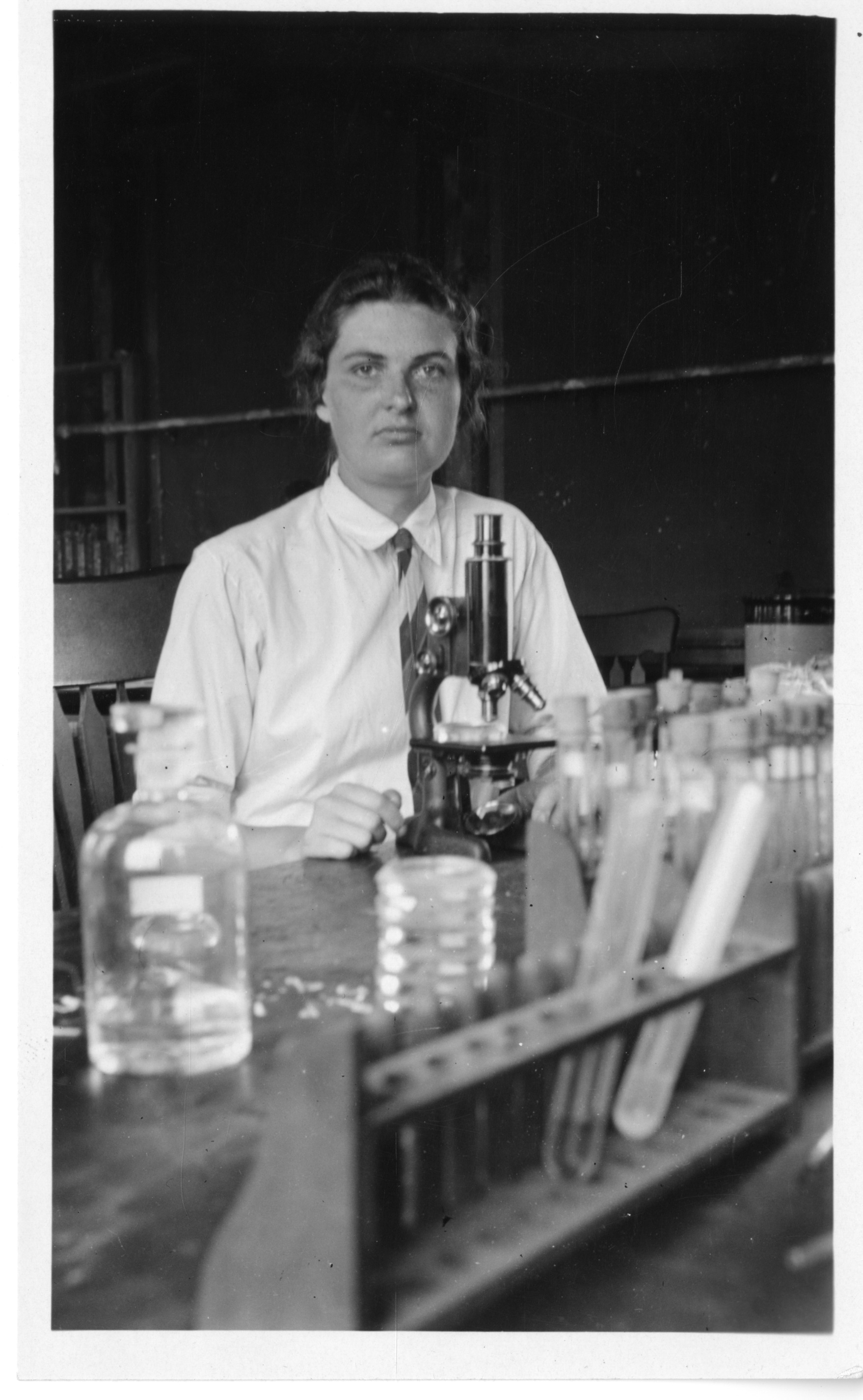 A person sitting at a desk looks directly into the camera. A microscope, test tubes, beakers, and ot