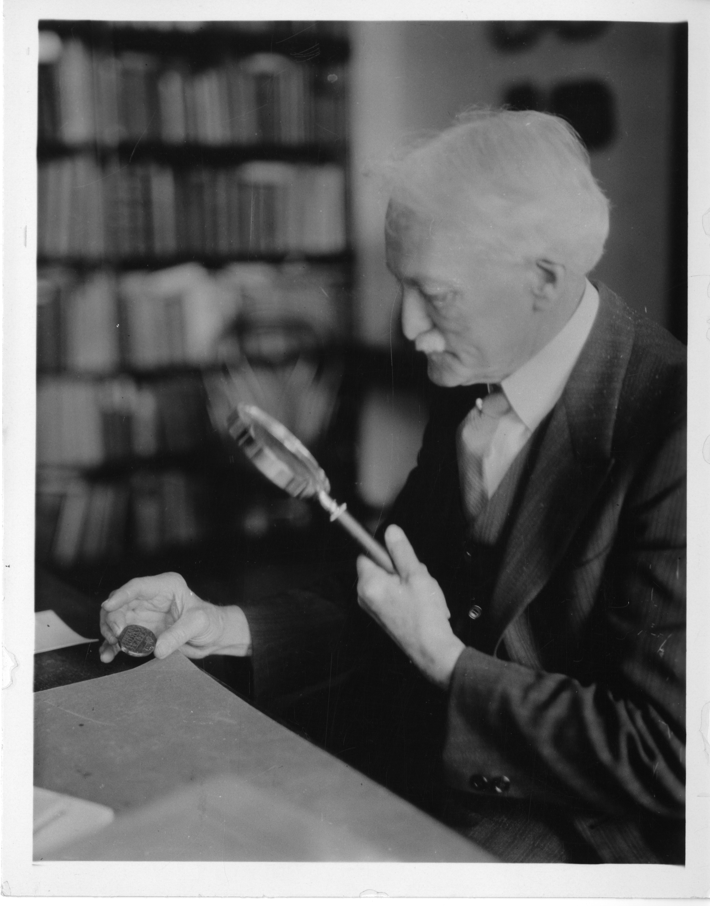 Walter Hough, anthropologist and ethnologist, holding coin in hand and looking at it through a magni