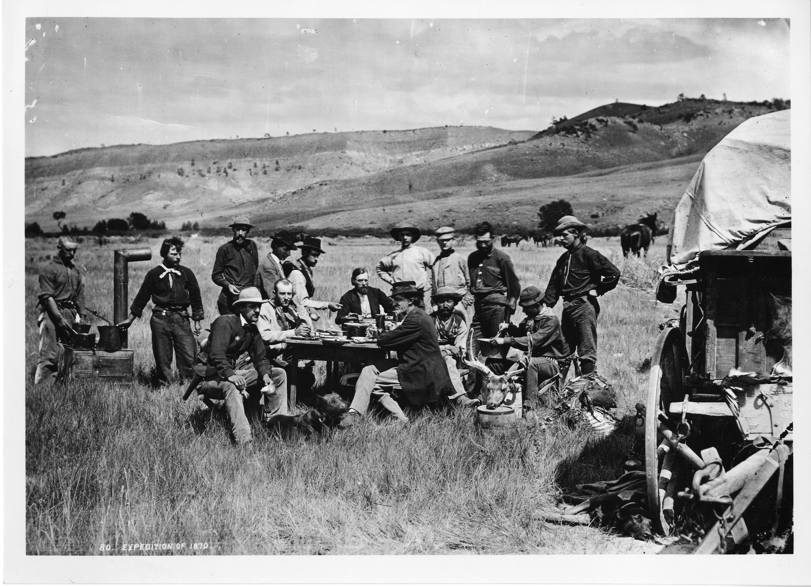 Men gather around a table at a campsite.
