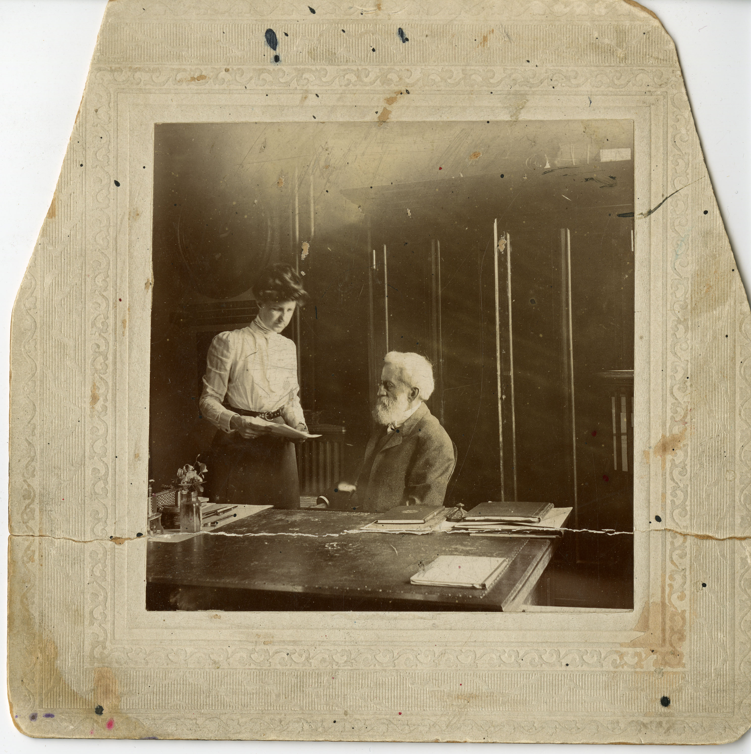 A man and woman interact. The man is sitting at a desk and the woman is standing and holding a piece
