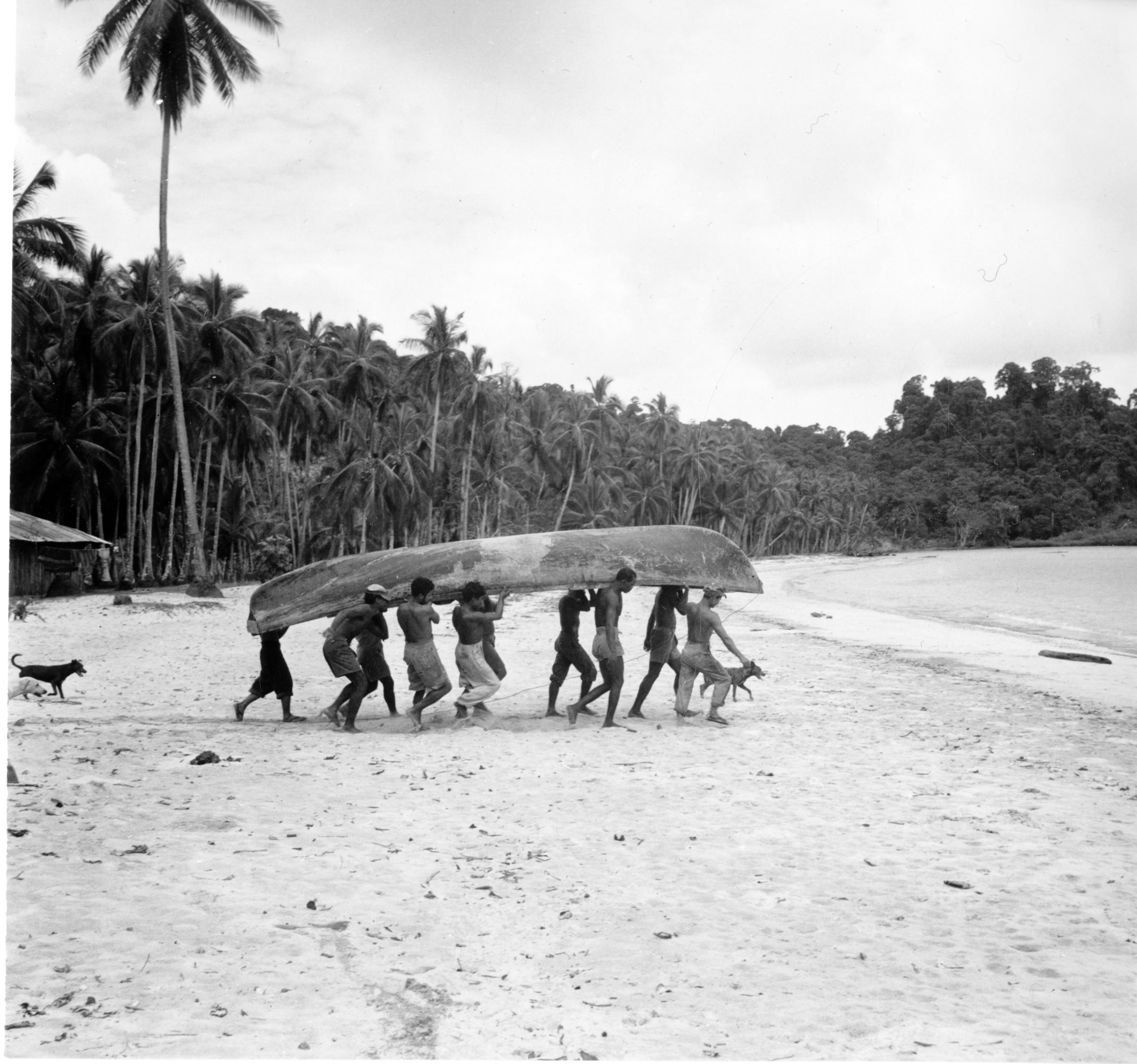 Black and white image of people carrying boat on a beach.
