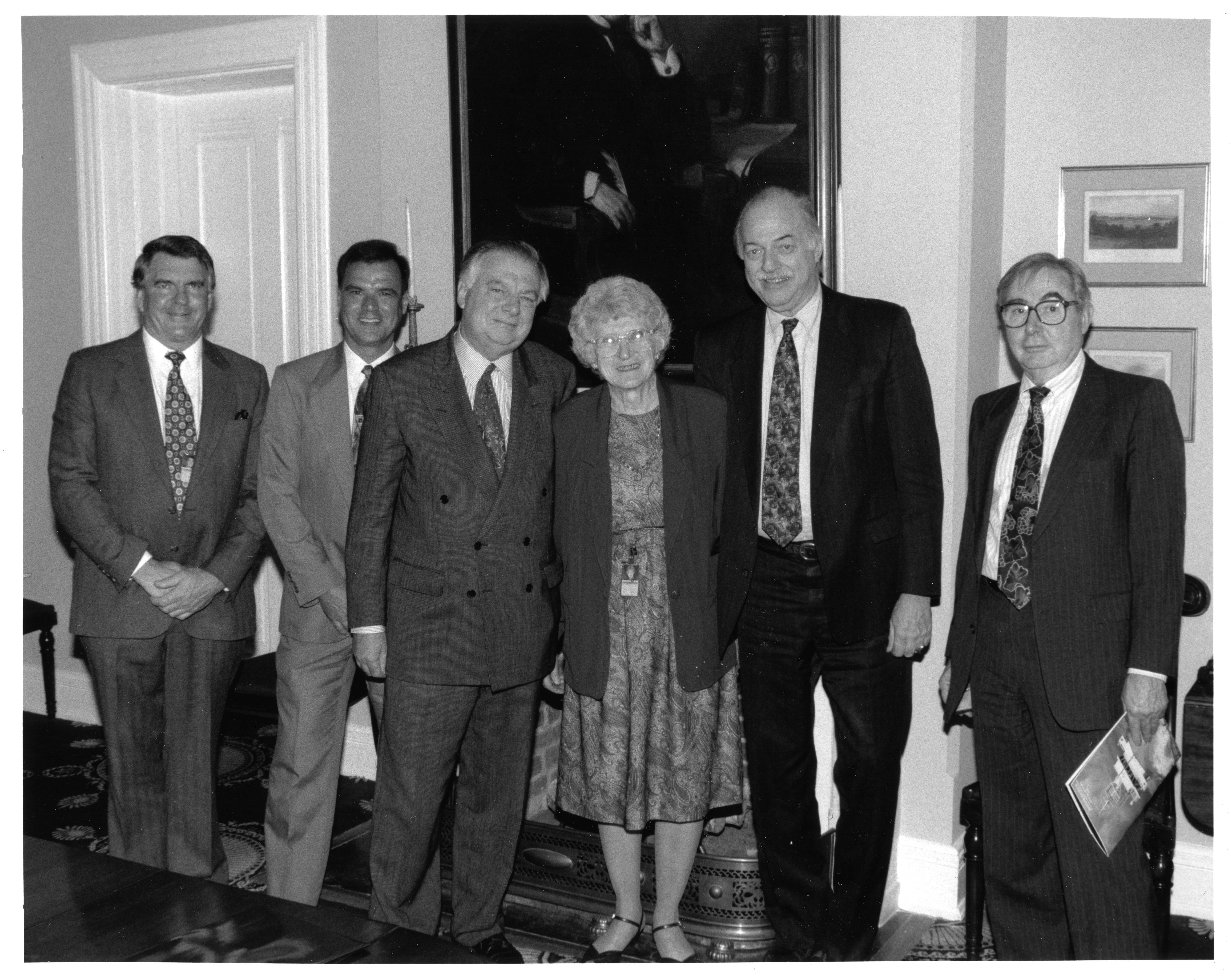 Mary Rice stands next to Secretary Adams and four other men.