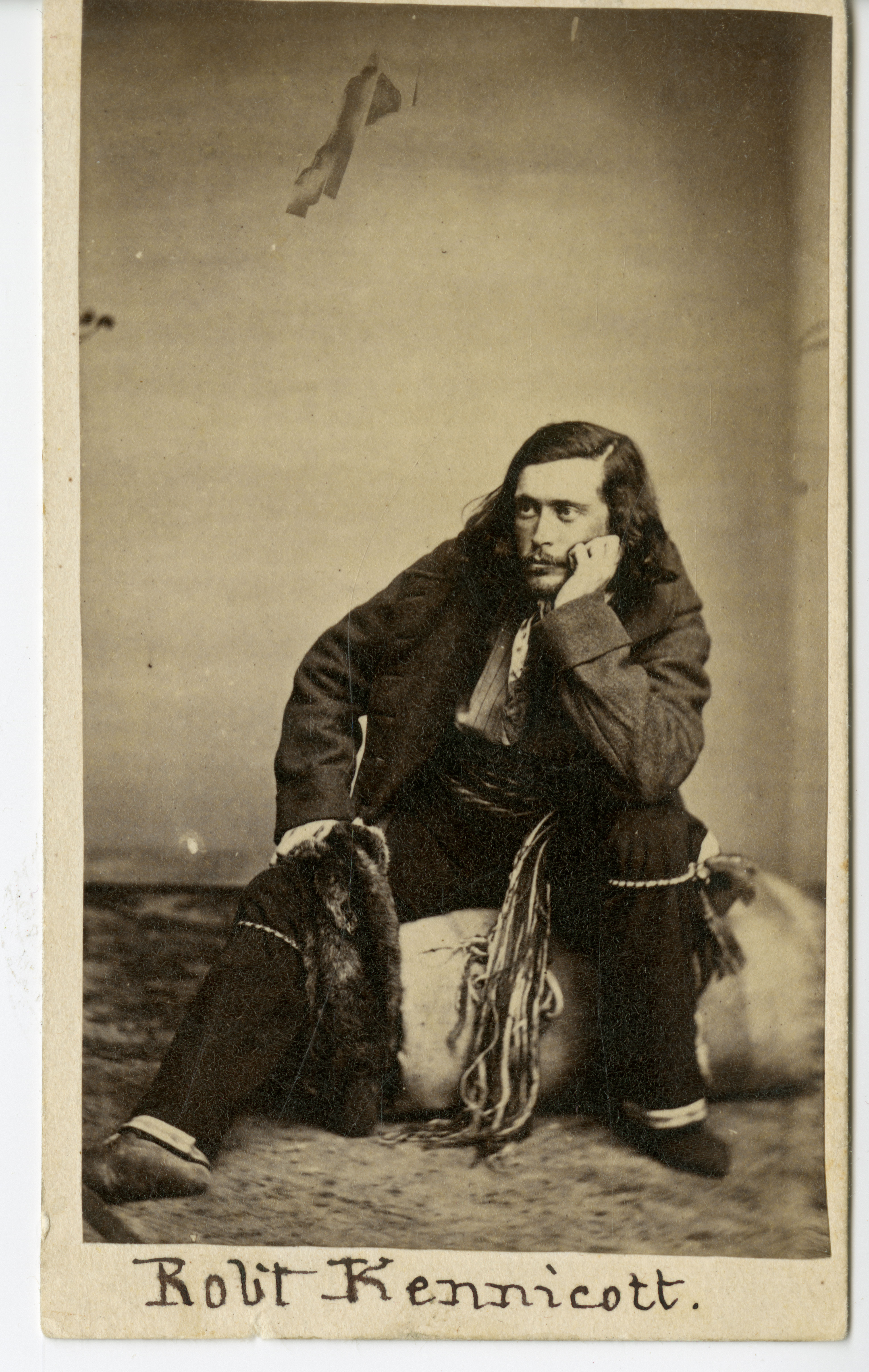 A portrait photograph of a man sitting, He is holding his chin up with a hand and is resting an elbo