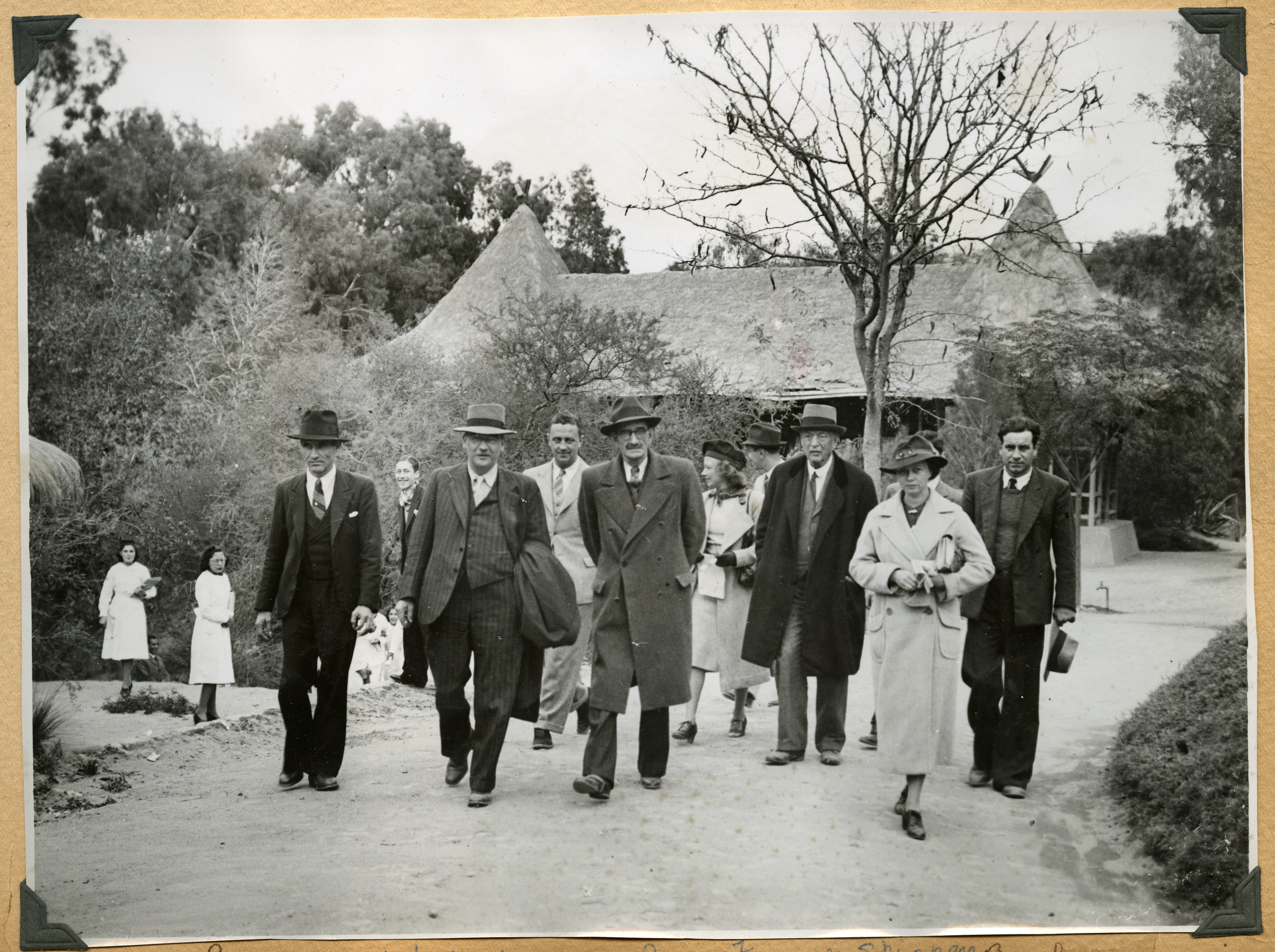 A group in hats and formal clothing walk on a road. Lucile Mann is in the front, to the right.