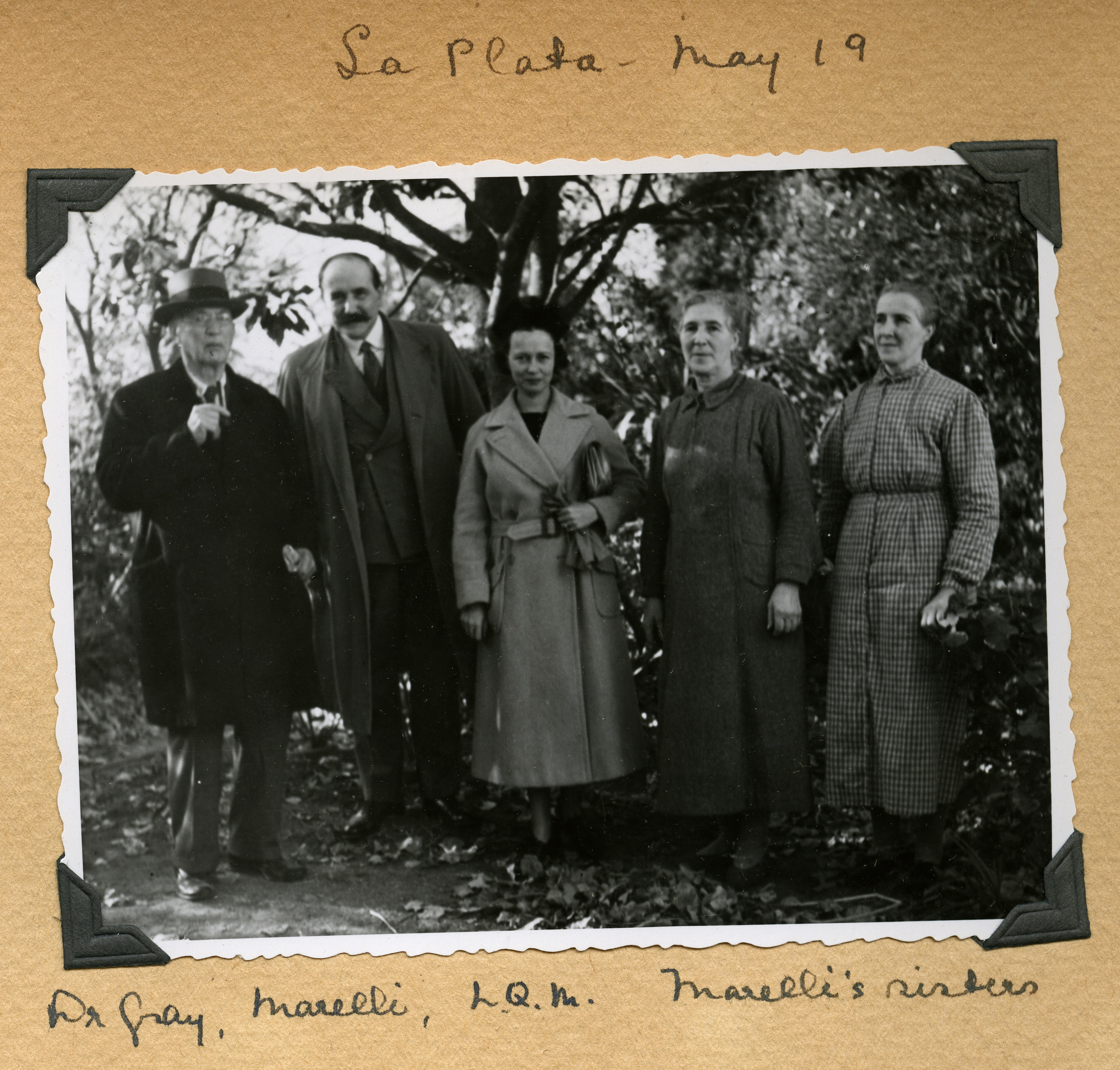Image in a scrapbook of a group standing outdoors but dressed fairly formally. There are three women
