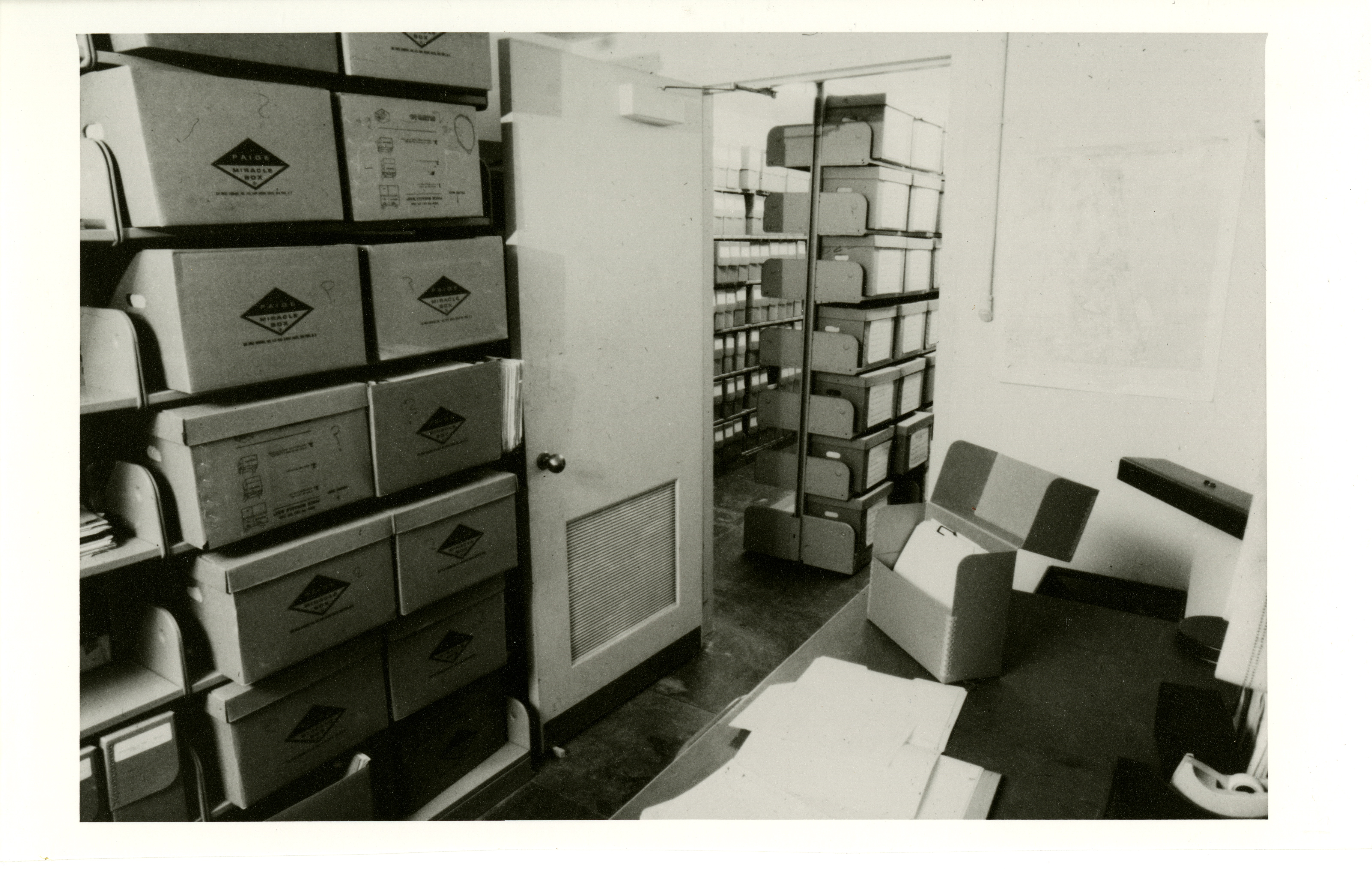 Black and white image of rows of shelves with boxes.