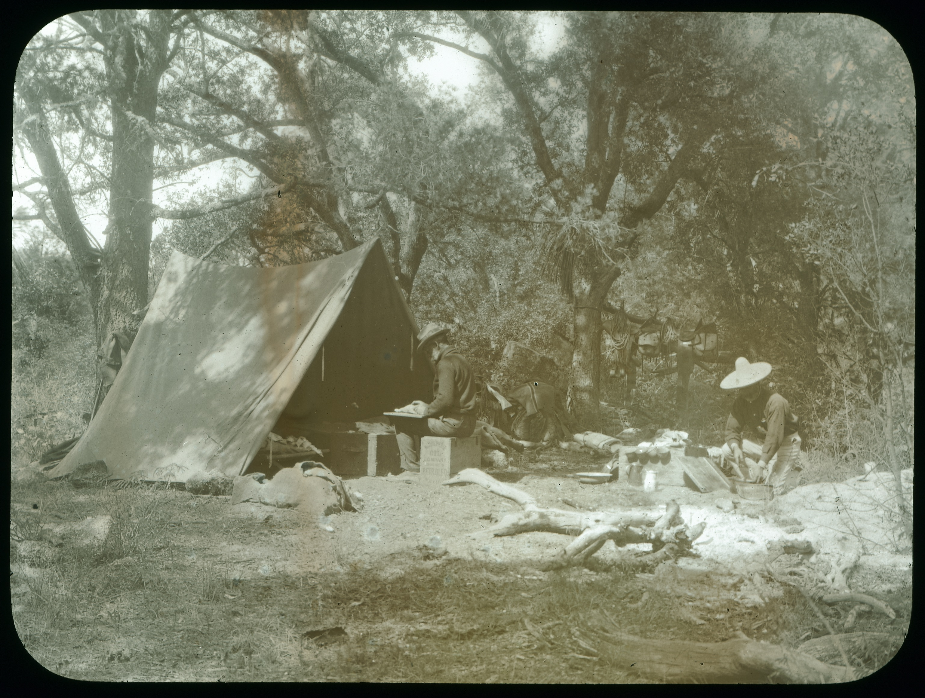 Two men work at a campsite. Their faces are not visible.