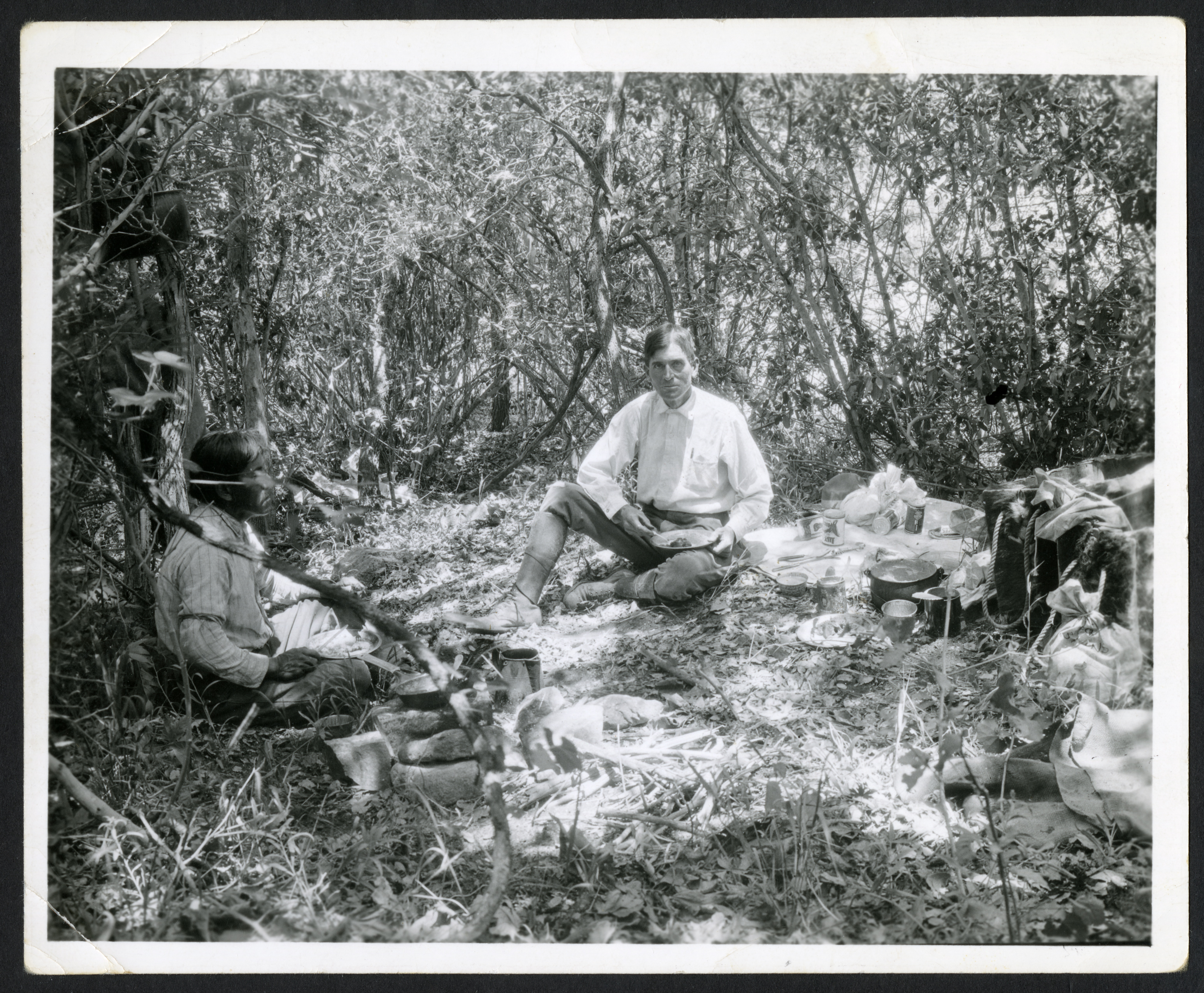 Two men sit in a field around pots and pans.