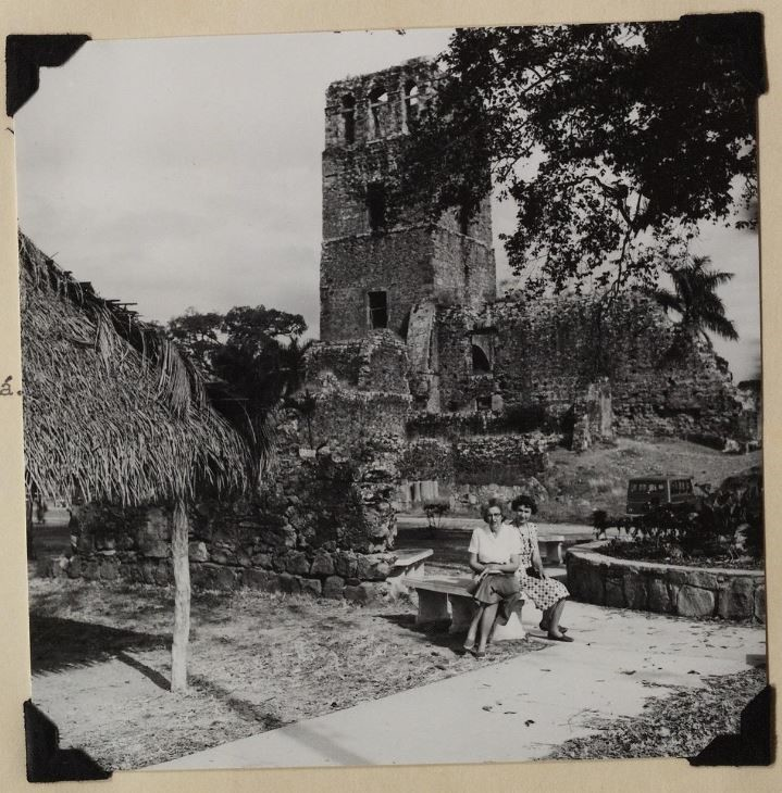 Beatrice Wetmore and Helena Weiss sitting on a bench with an old tower behind them in old Panama Cit