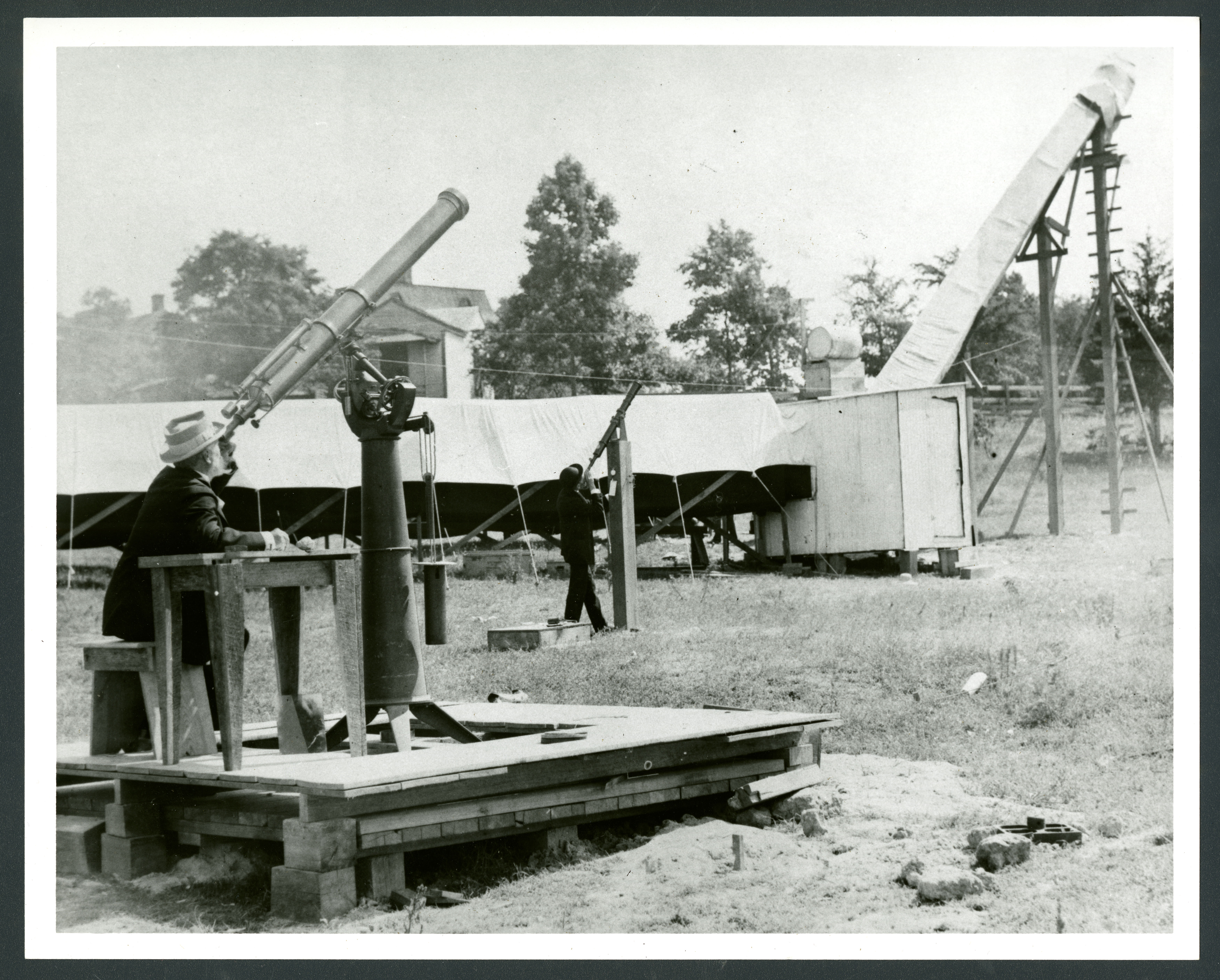 Two men stand in a field and look through two telescopes.