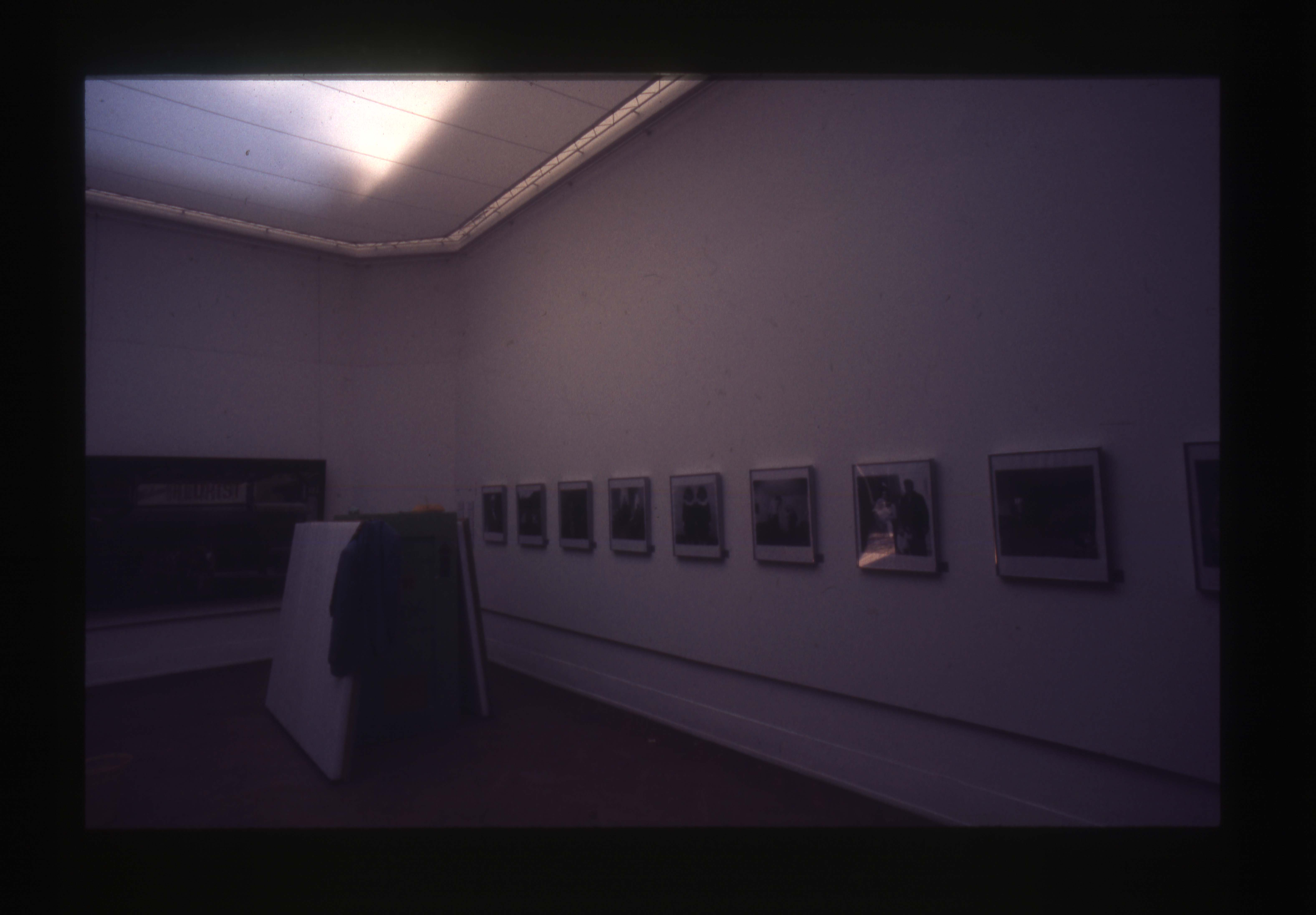 Color photo of a gallery with white walls, hanging in a single row across the walls are photographs.