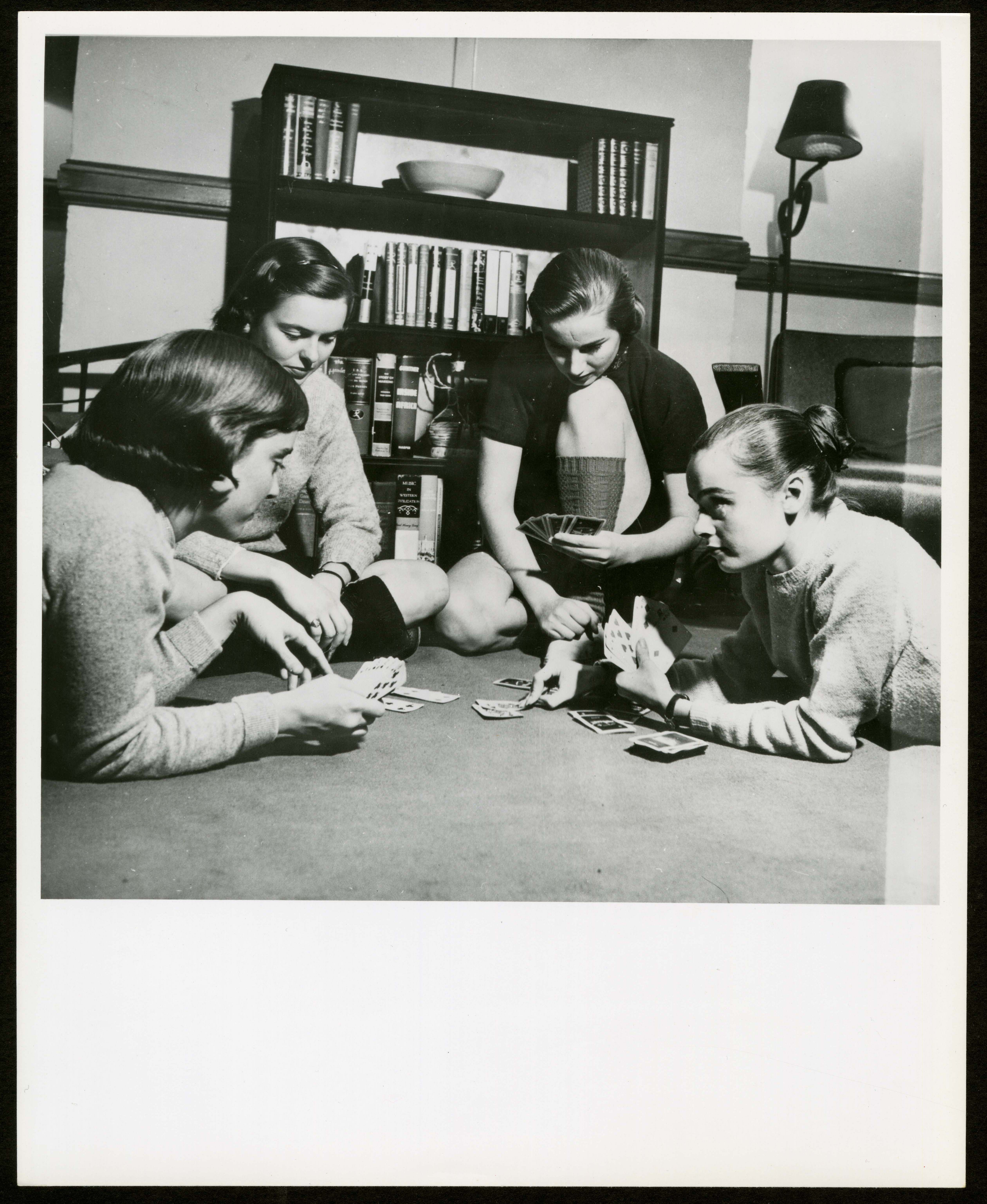 B & W image of four young female students playing cards on the floor.