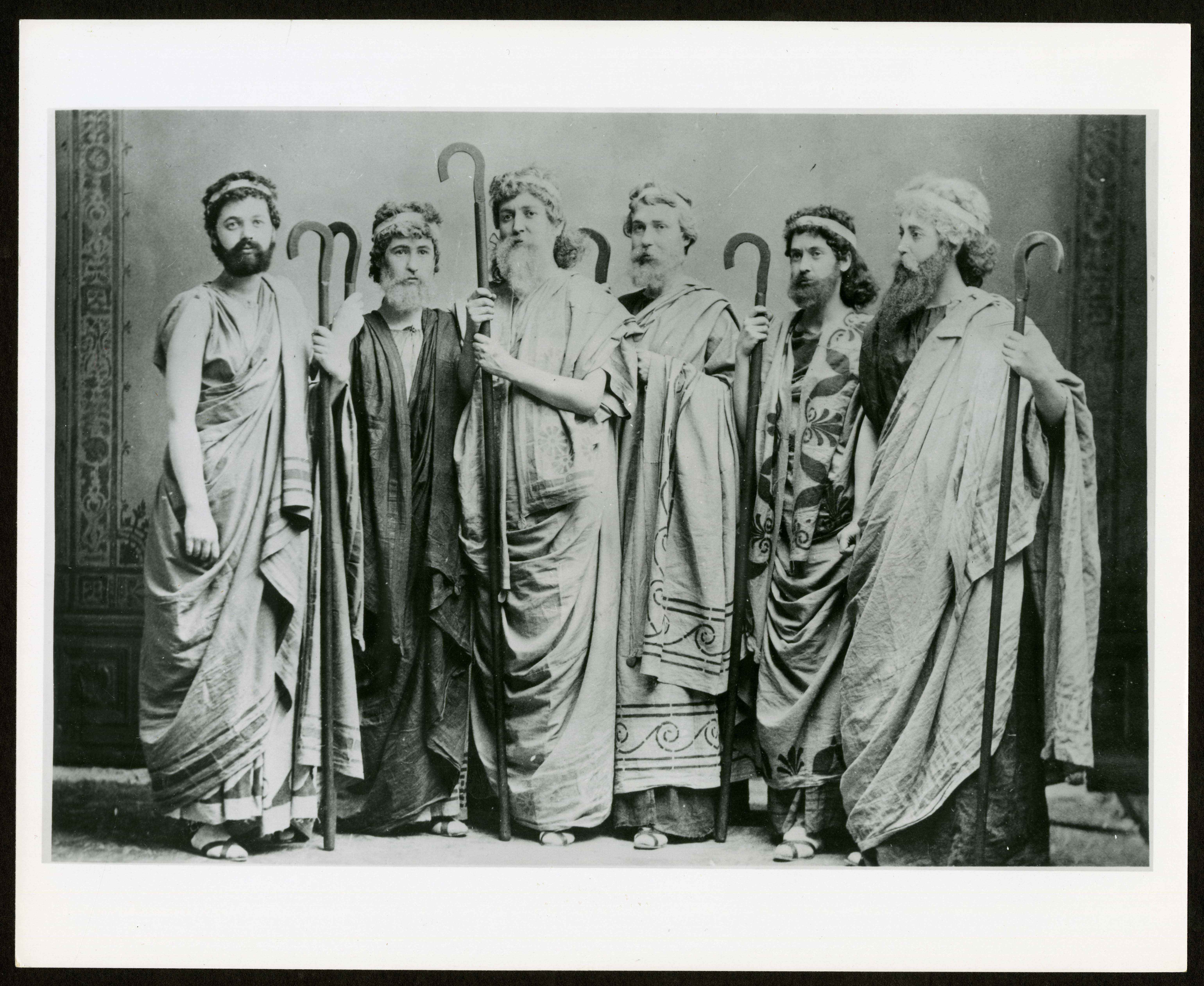 B & W image of six women dressed in ancient Greek style togas, and wearing fake beards, holding
