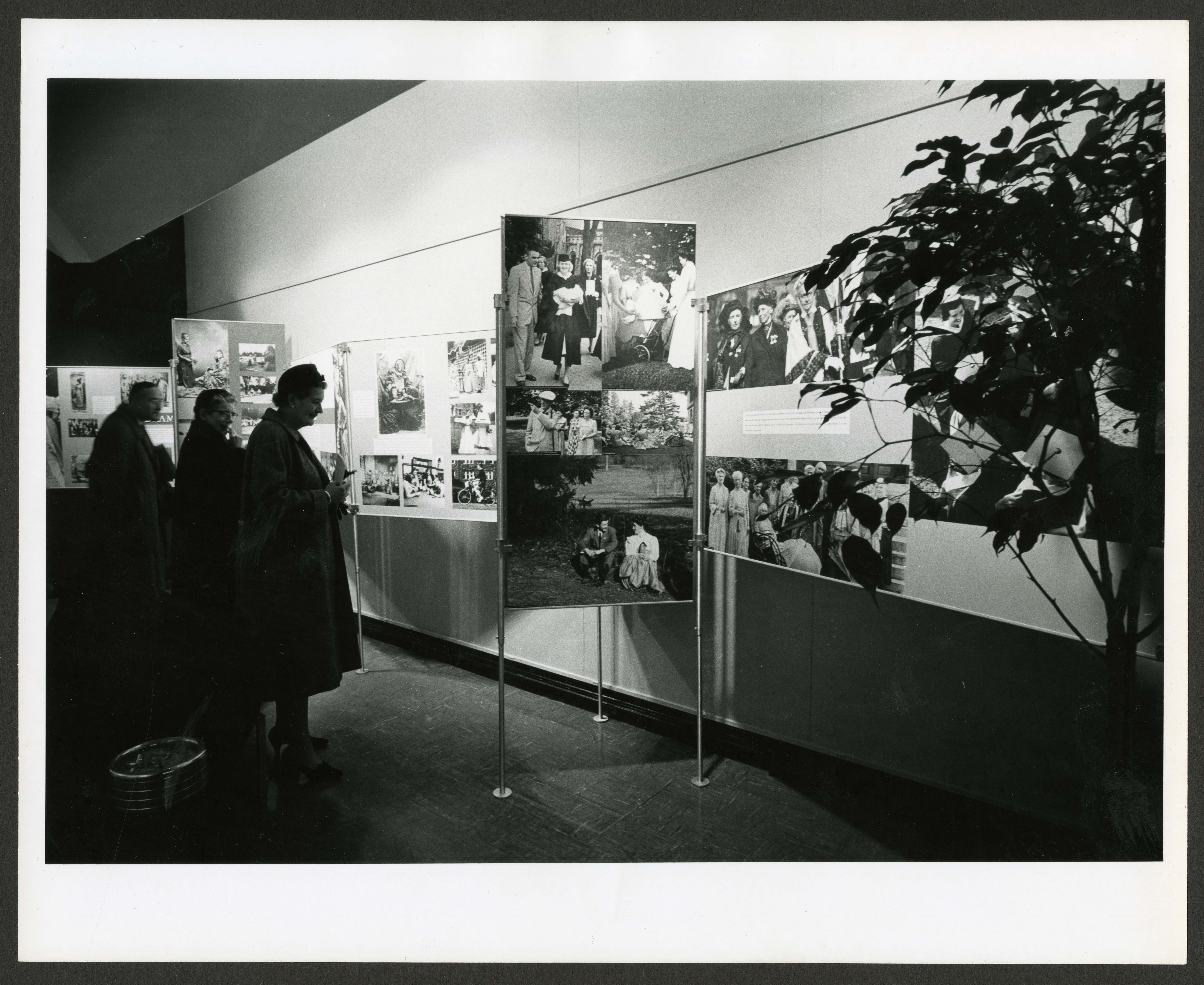 B & W image of three museum visitors viewing several museum panels.