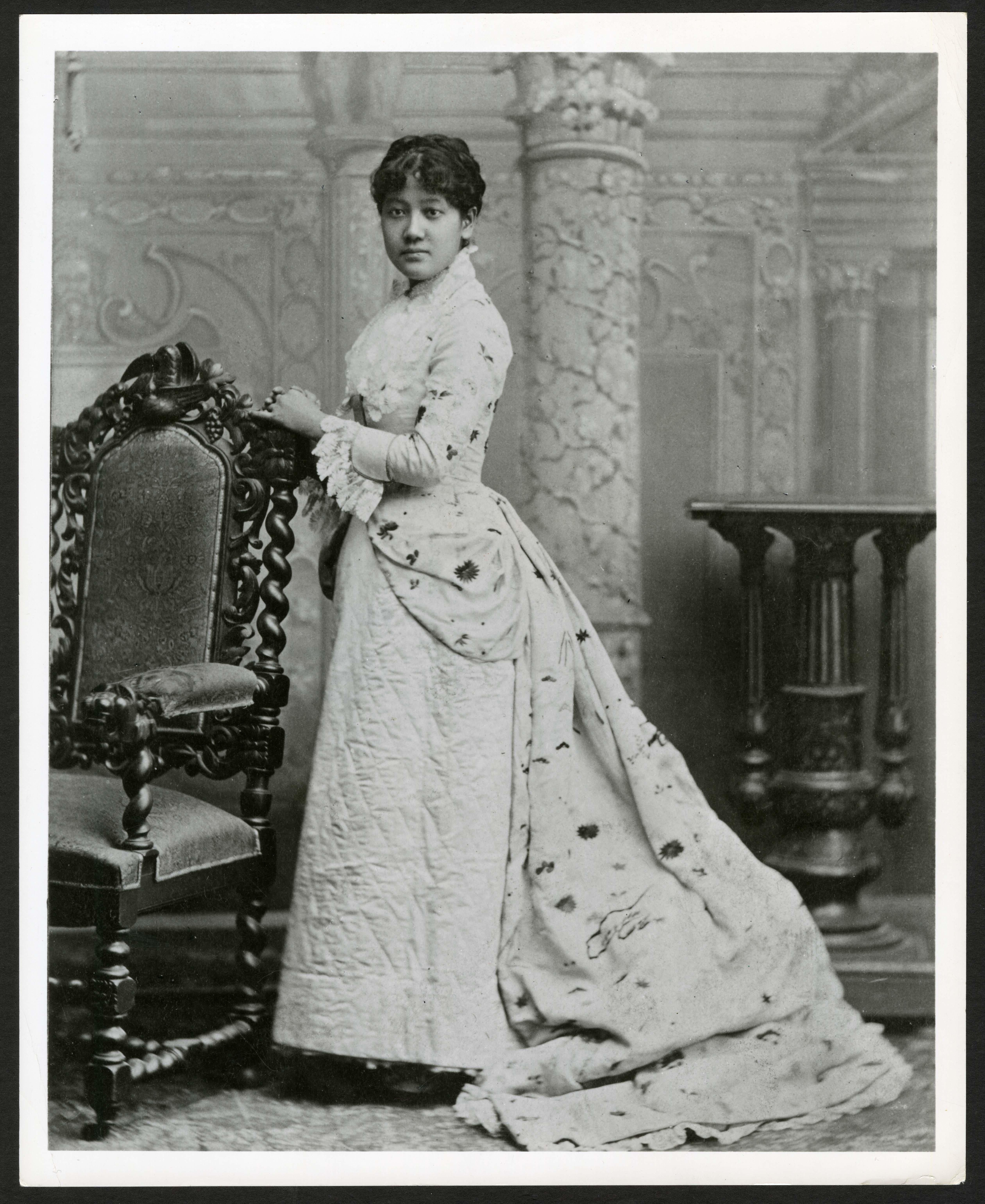 B & W portrait of Stematz Yamakawa standing, wearing a long dress.