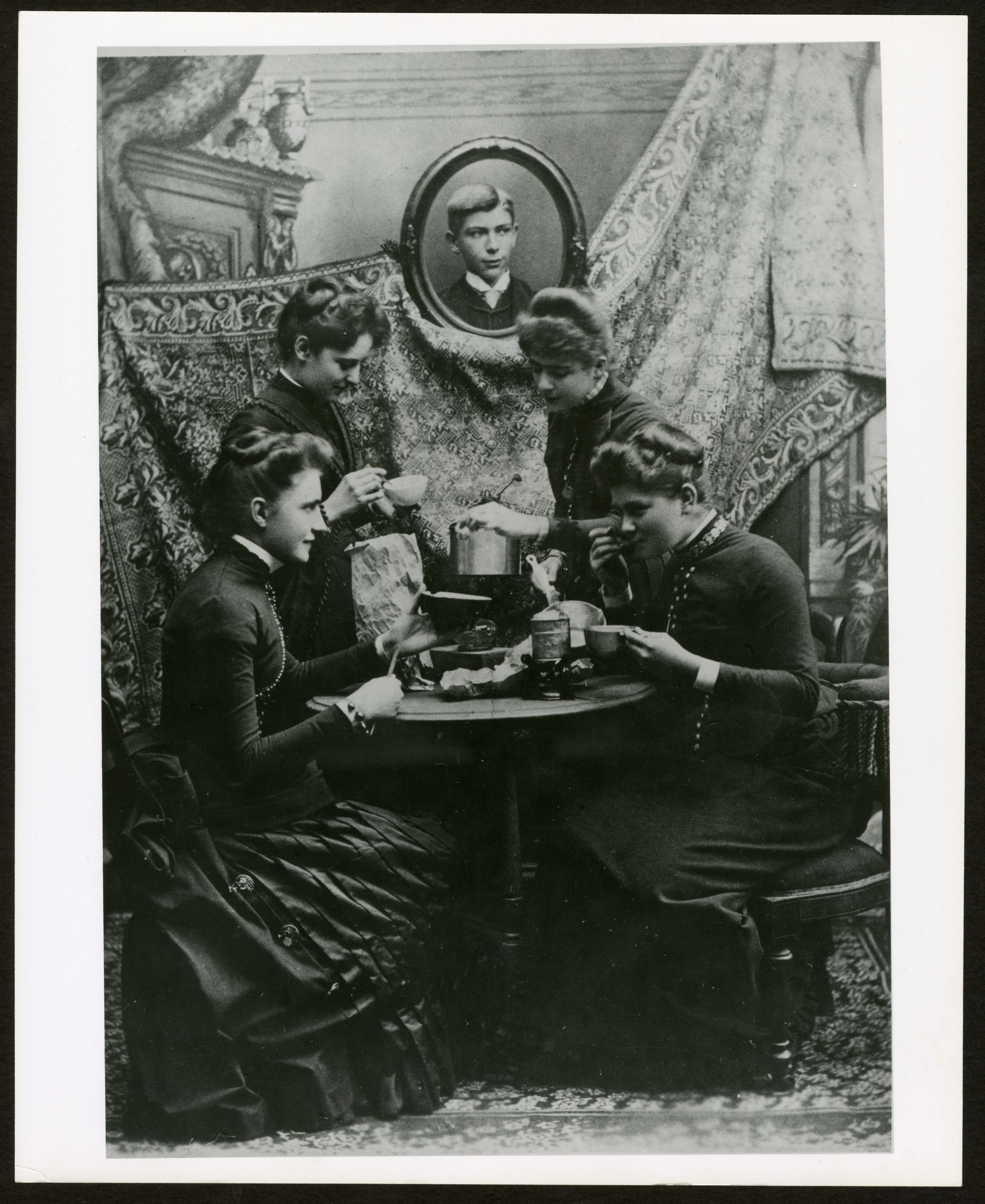 B & W image of four female students around a table. Two are eating, and tow are preparing tea.