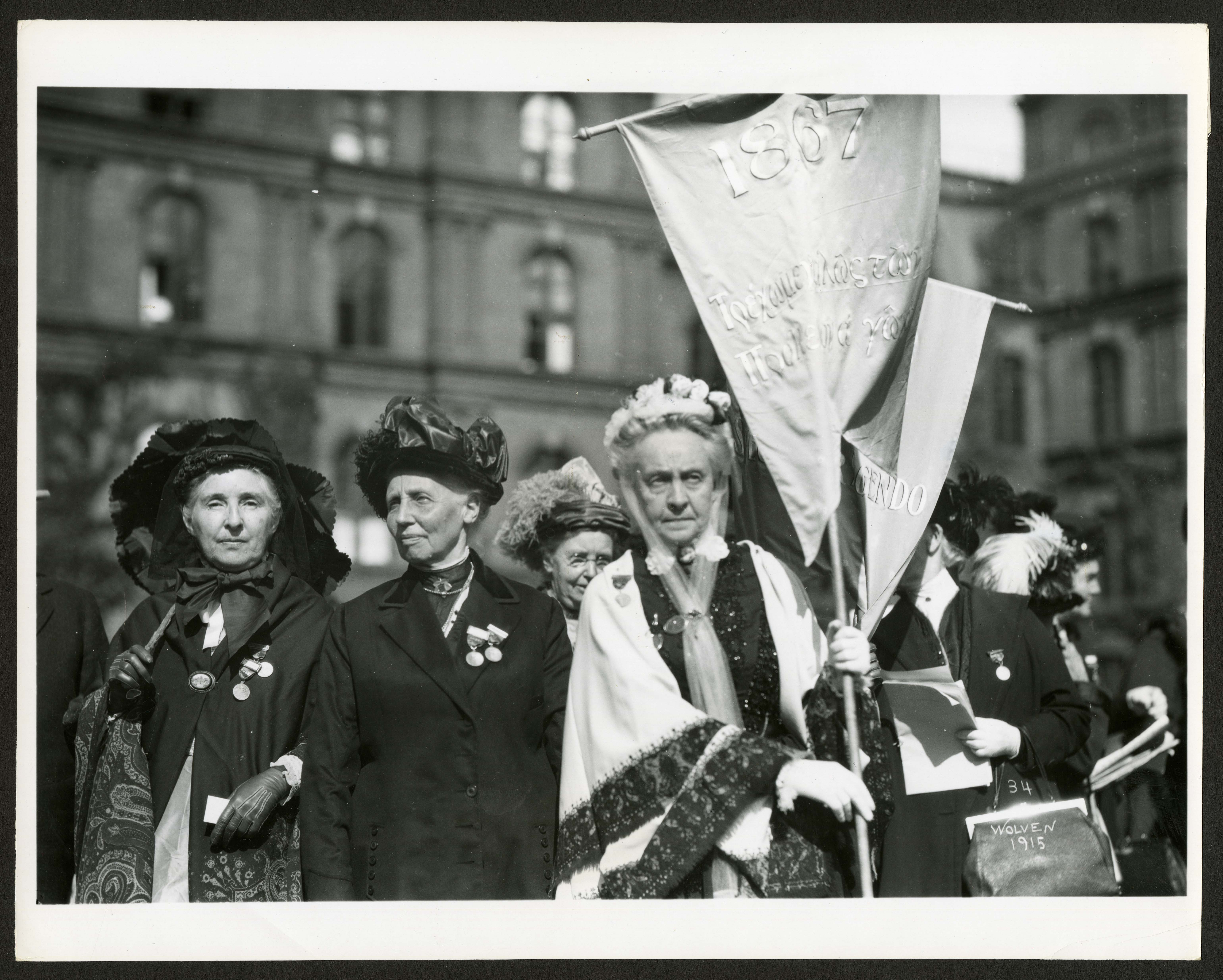 B & W image of three older women, standing outside in front of a crowd of other women. One woman