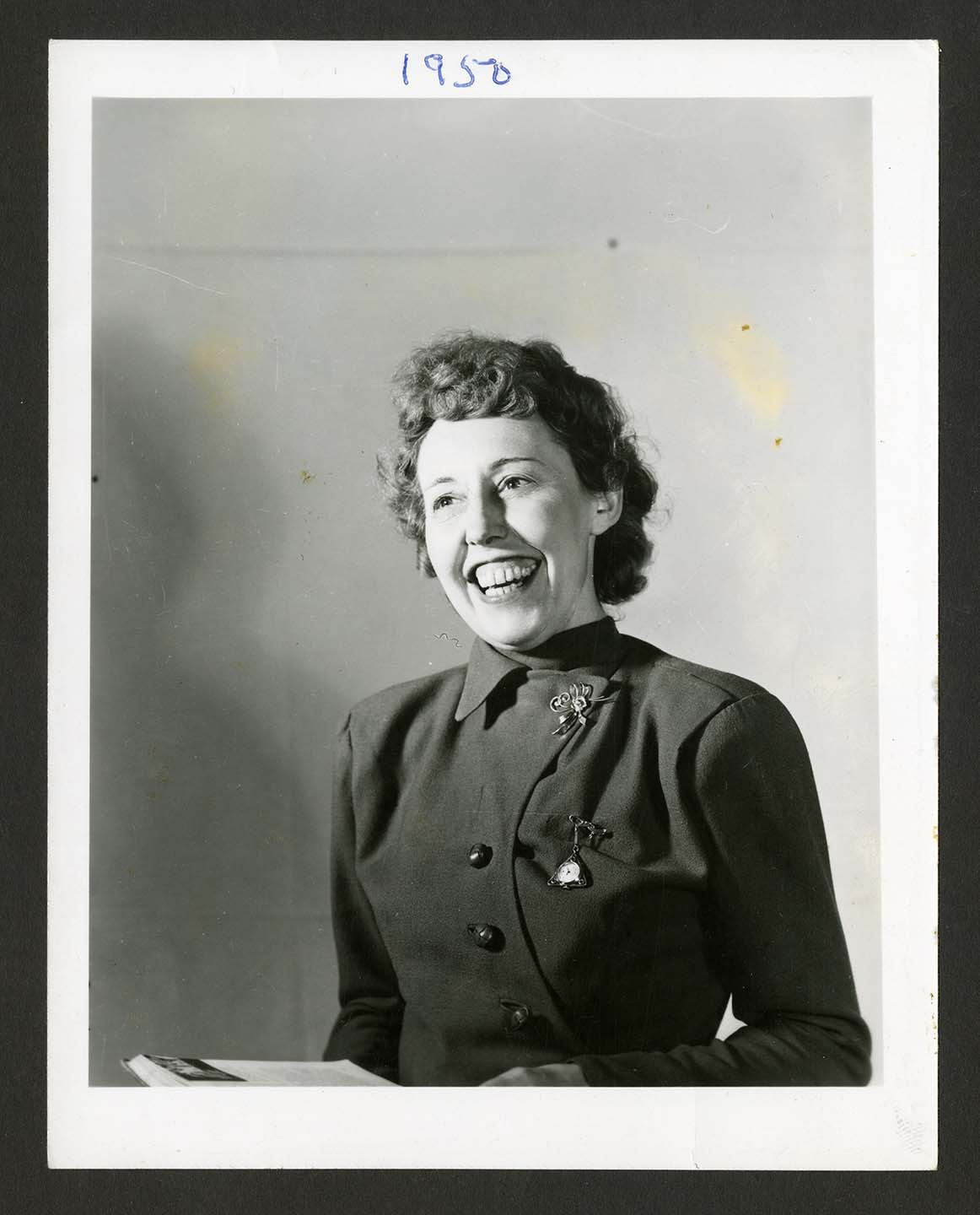 Portrait photograph of a woman smiling widely. She is wearing two pins on her collared dress.