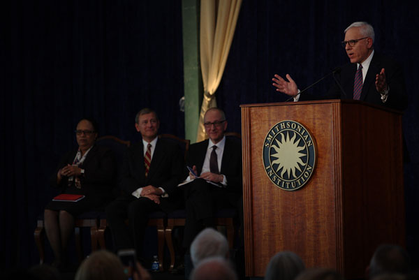 Installation of Dr. David Skorton  with David M. Rubenstein, Board of Regents, speaking at the podium. David J. Skorton is second from the right. National Museum of American History, Photographic Files, DAMS.si.edu.