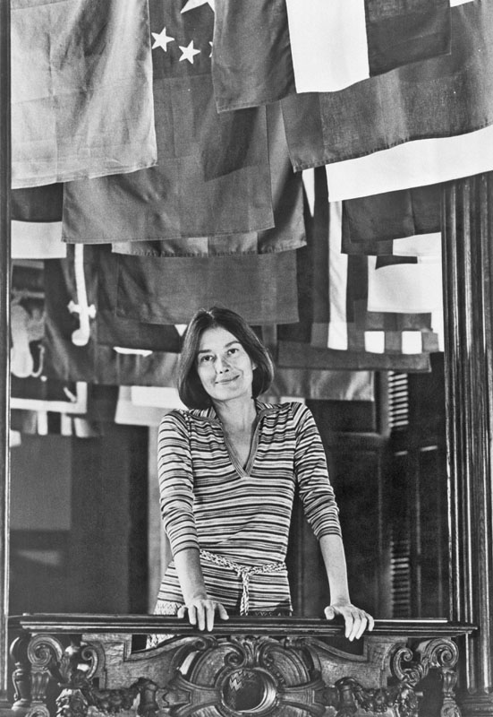 Lisa Taylor, the director of the Cooper-Hewitt Museum of Decorative Arts and Design stands in front of a display of flags from the 'MAN transFORMS' exhibition. Smithsonian Institution Archives, Record Unit 287, Box 18, Folder 13.