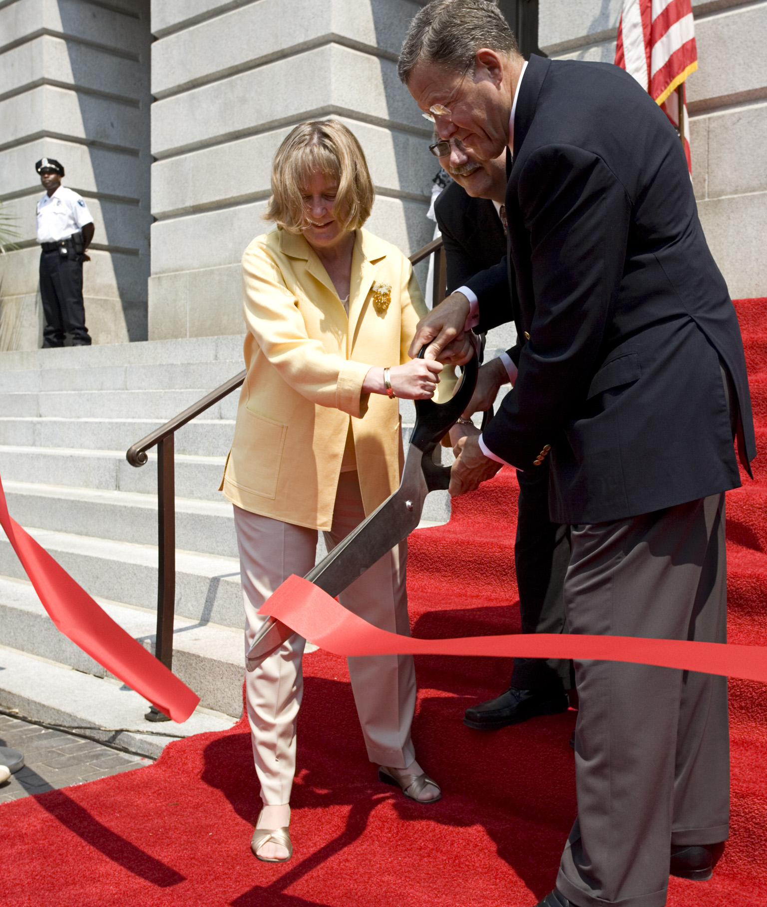 Three people cut a red ribbon with a large pair of scissors.
