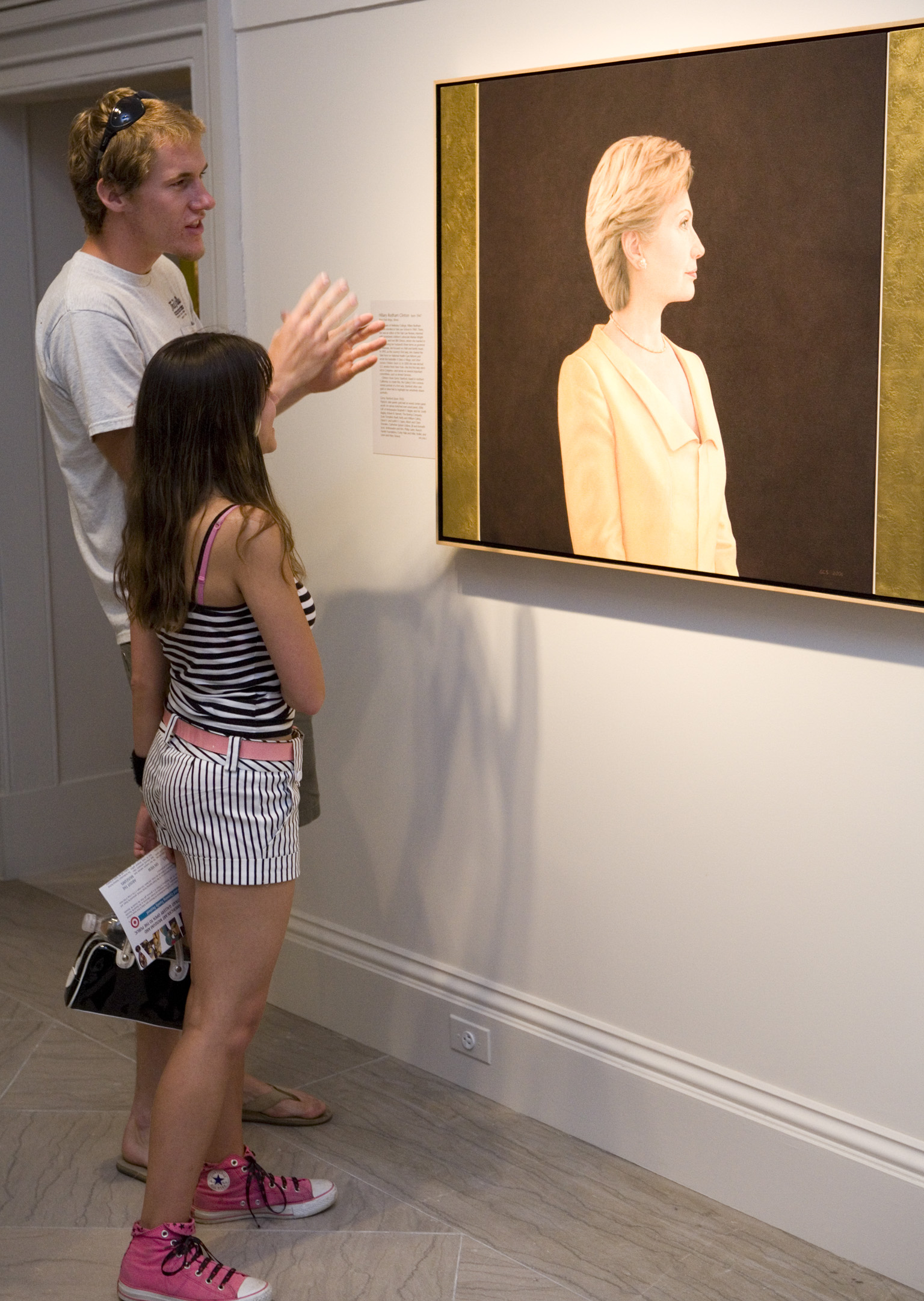 A man and woman look at a portrait of Hillary Rodham Clinton.