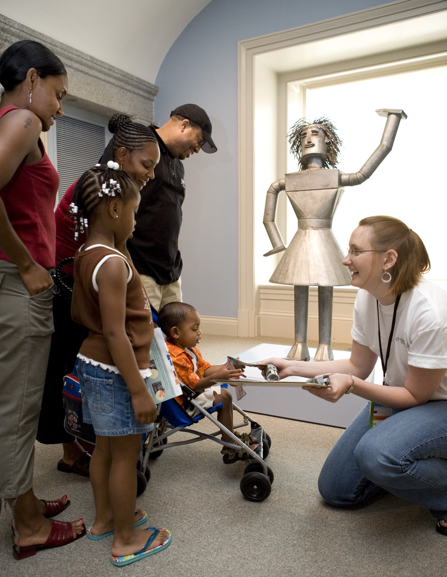 A family with a baby in a stroller receives a flyer from a woman in front of a metal sculpture.