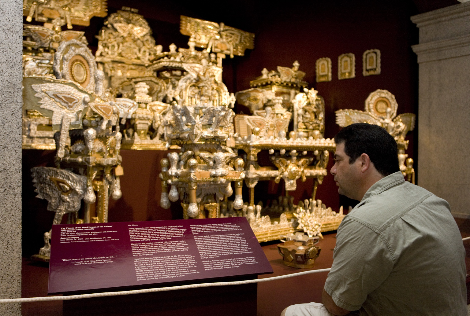 A man looks at an art piece of various items wrapped in foils.