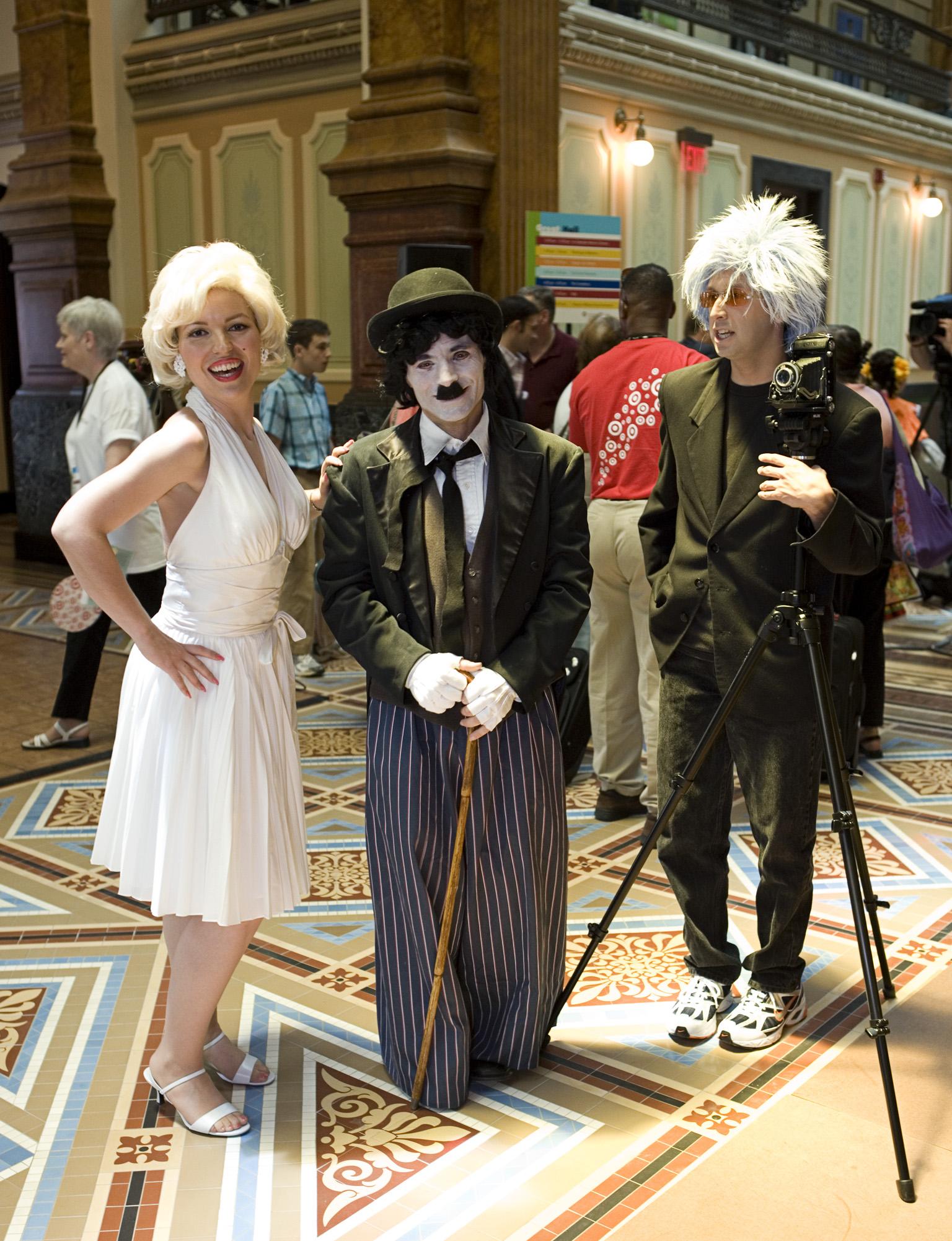 Three people dressed as Marilyn Monroe, left, Charlie Chaplin, and Andy Warhol